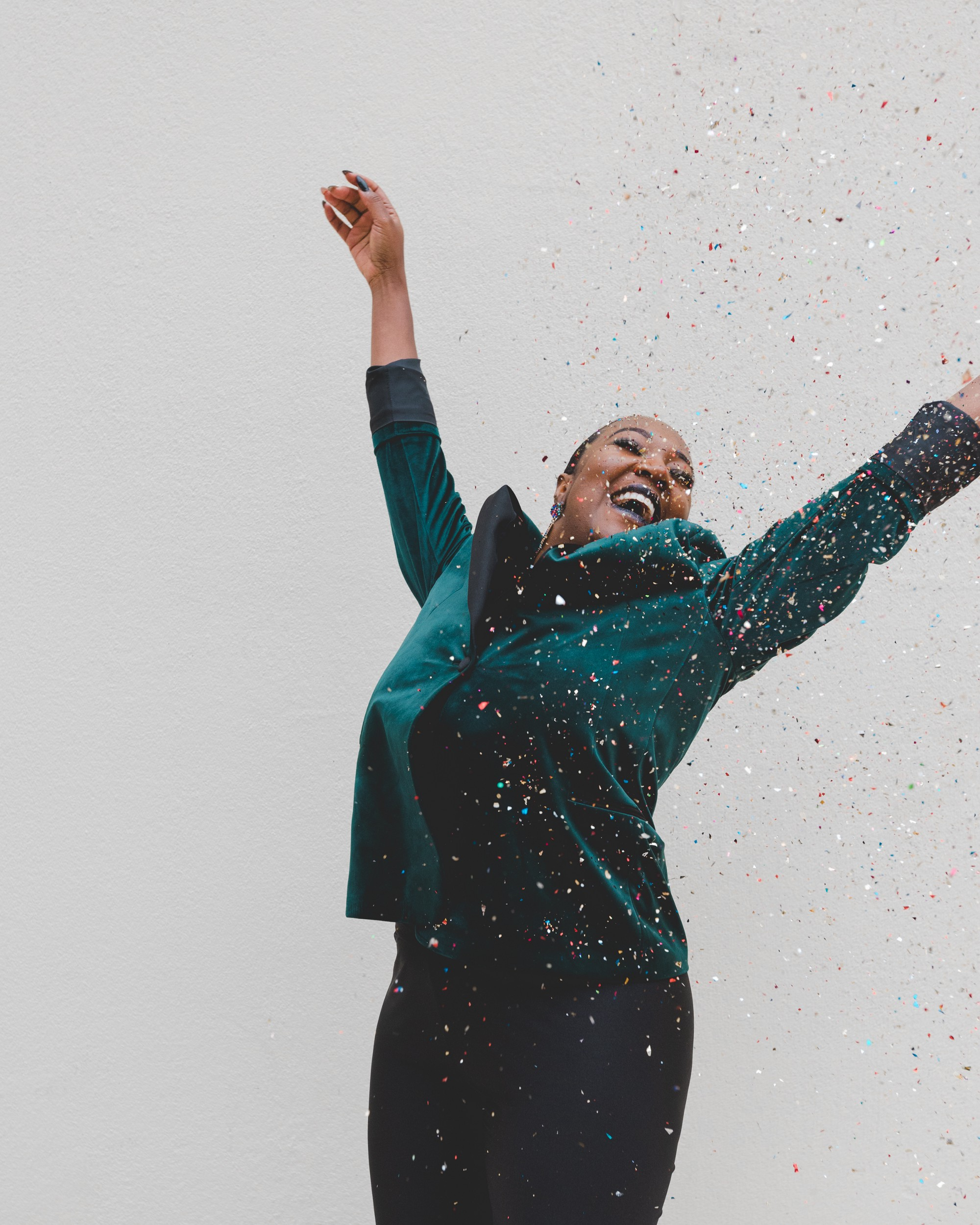 Lady in teal jacket jumping for joy as confetti blows over her. She gets paid $1 per word for freelance writing