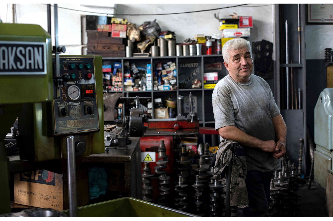 Elderly man standing in a workshop in dirty work clothes.