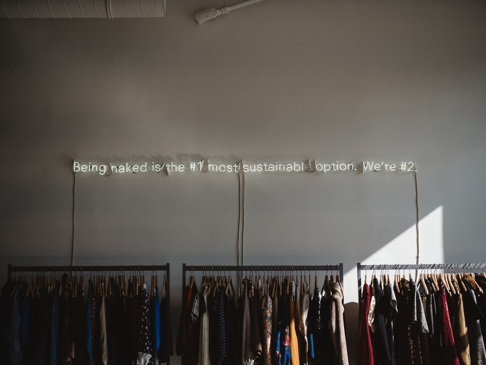 Neon lights above a clothing rack that reads: being naked is the #1 most sustainable option. we're #2.