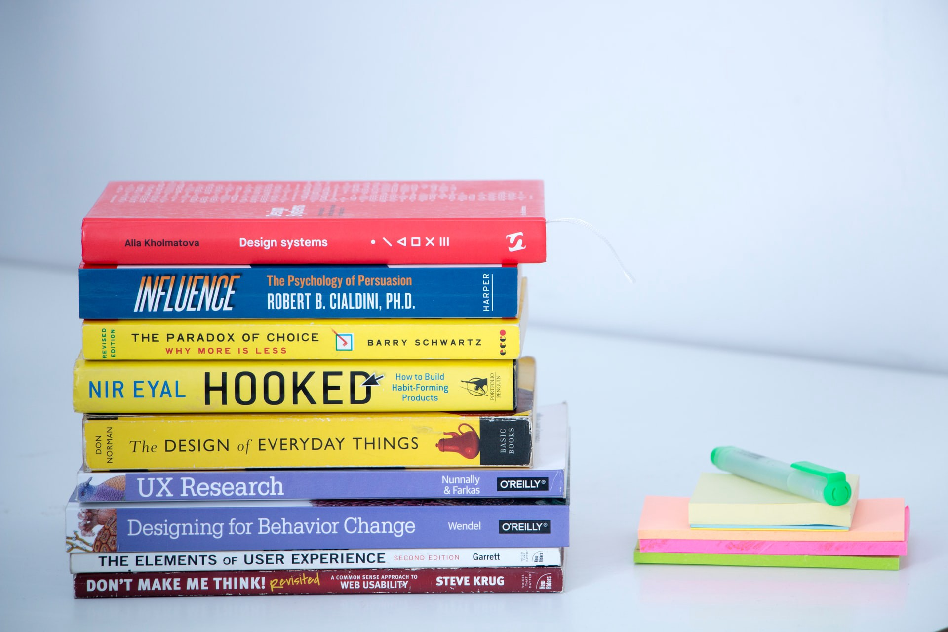 A pile of books about design, usability, and user experience, next to a pile of post-it notes and a pen.