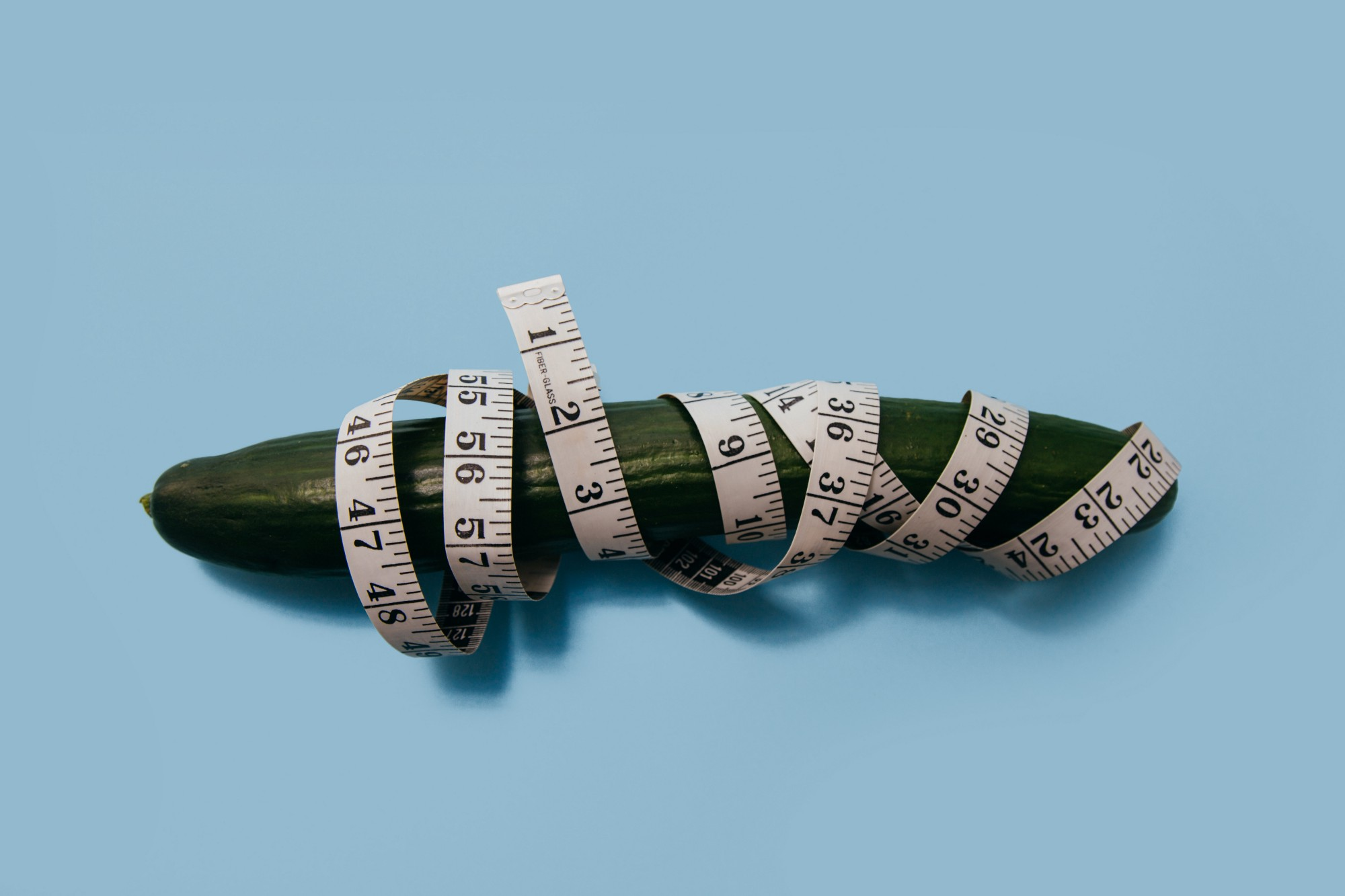A measuring tape is wrapped around a cucumber.