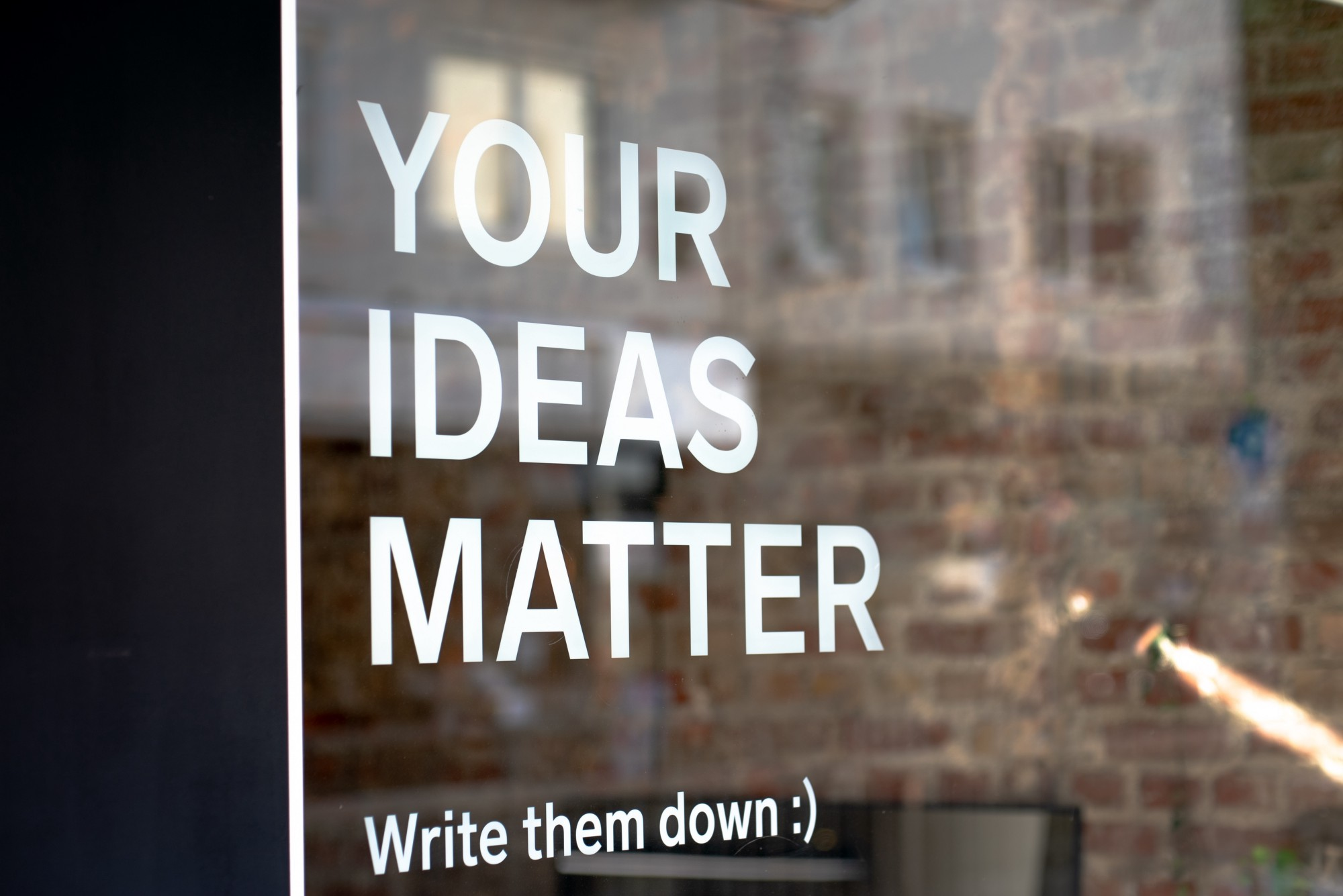 """Sign on glass says """"Your Ideas Matter, Write Them Down"""""""
