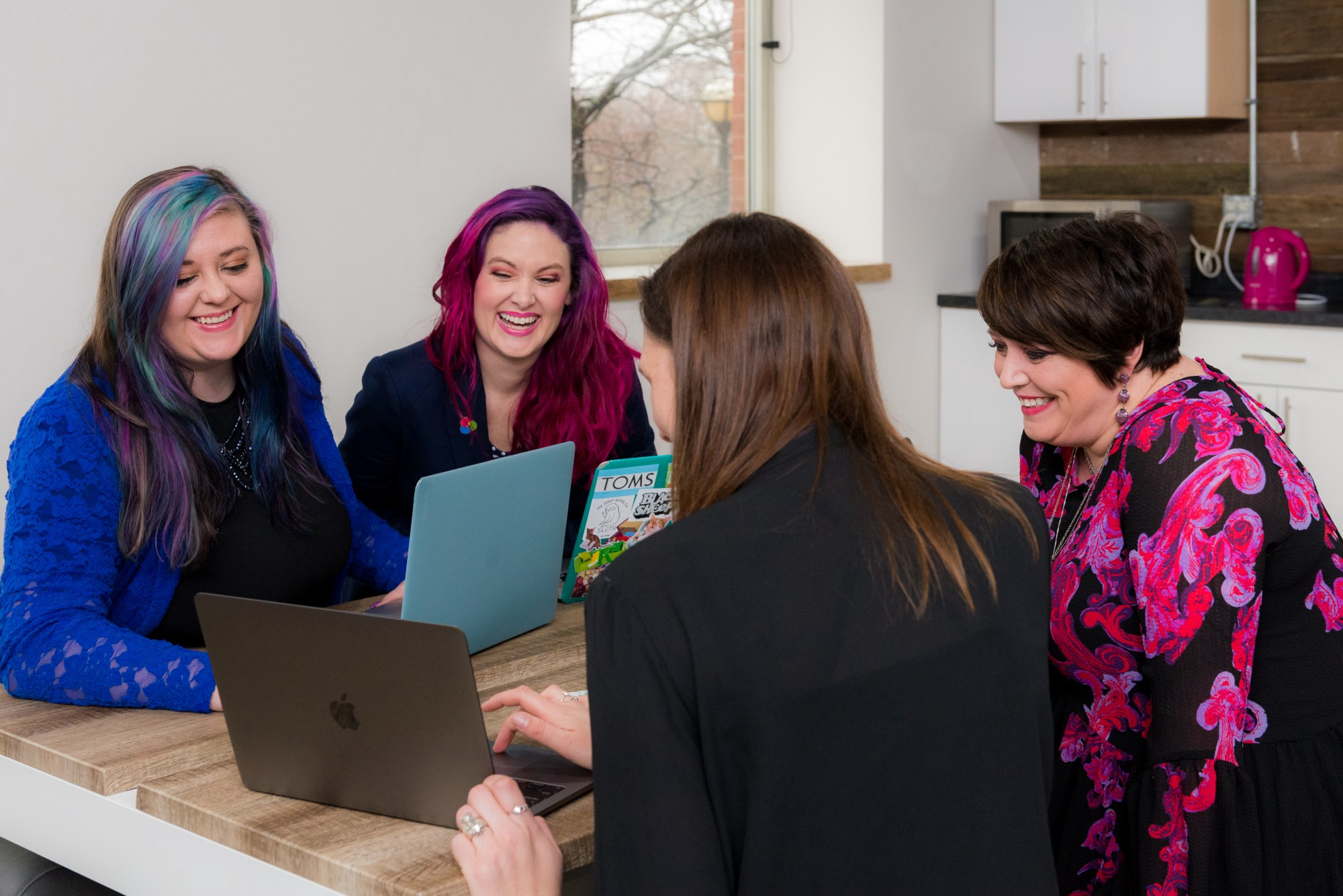four female employees smiling and looking at a laptop while all at a table.