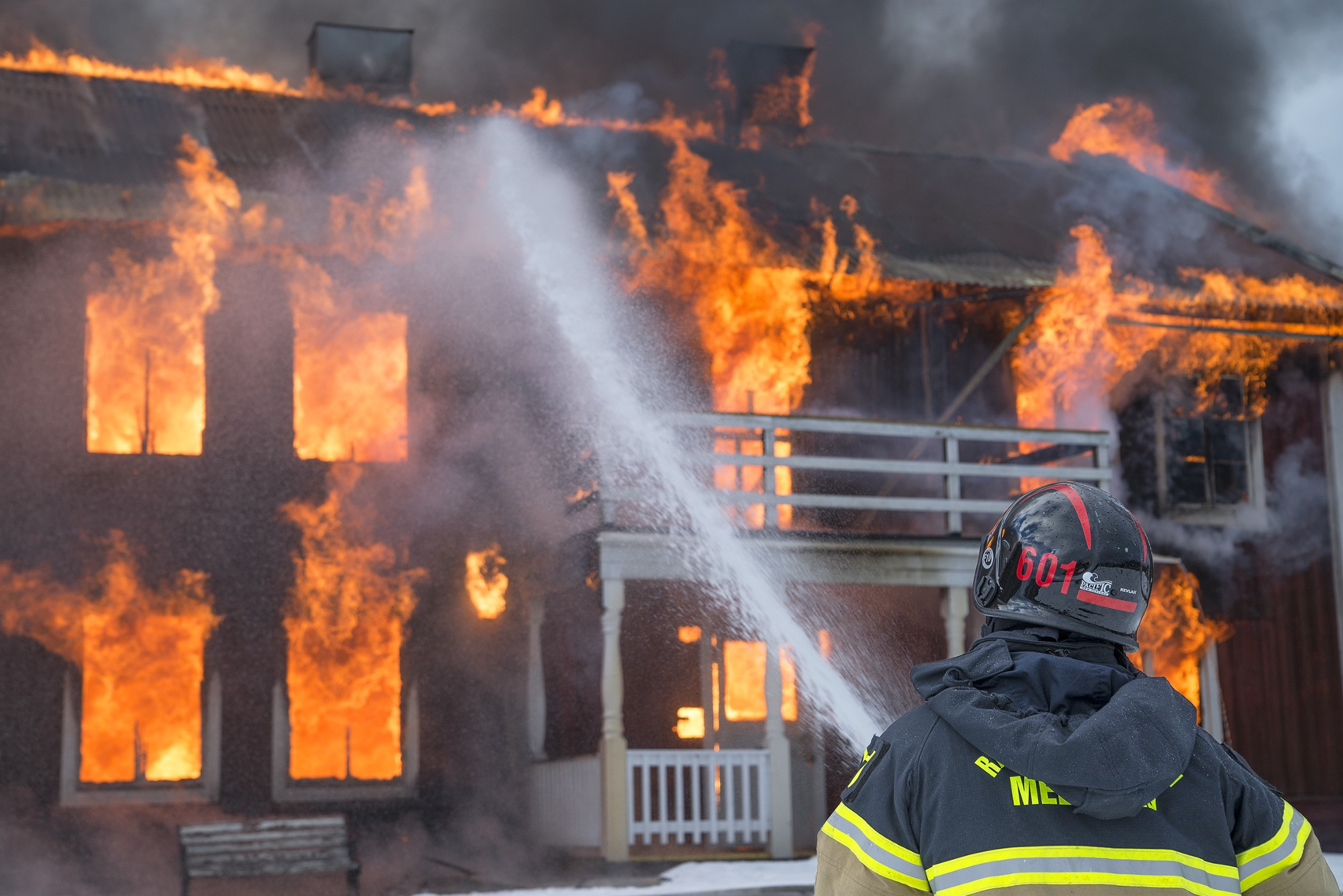 Fireman spraying water at a house on fire