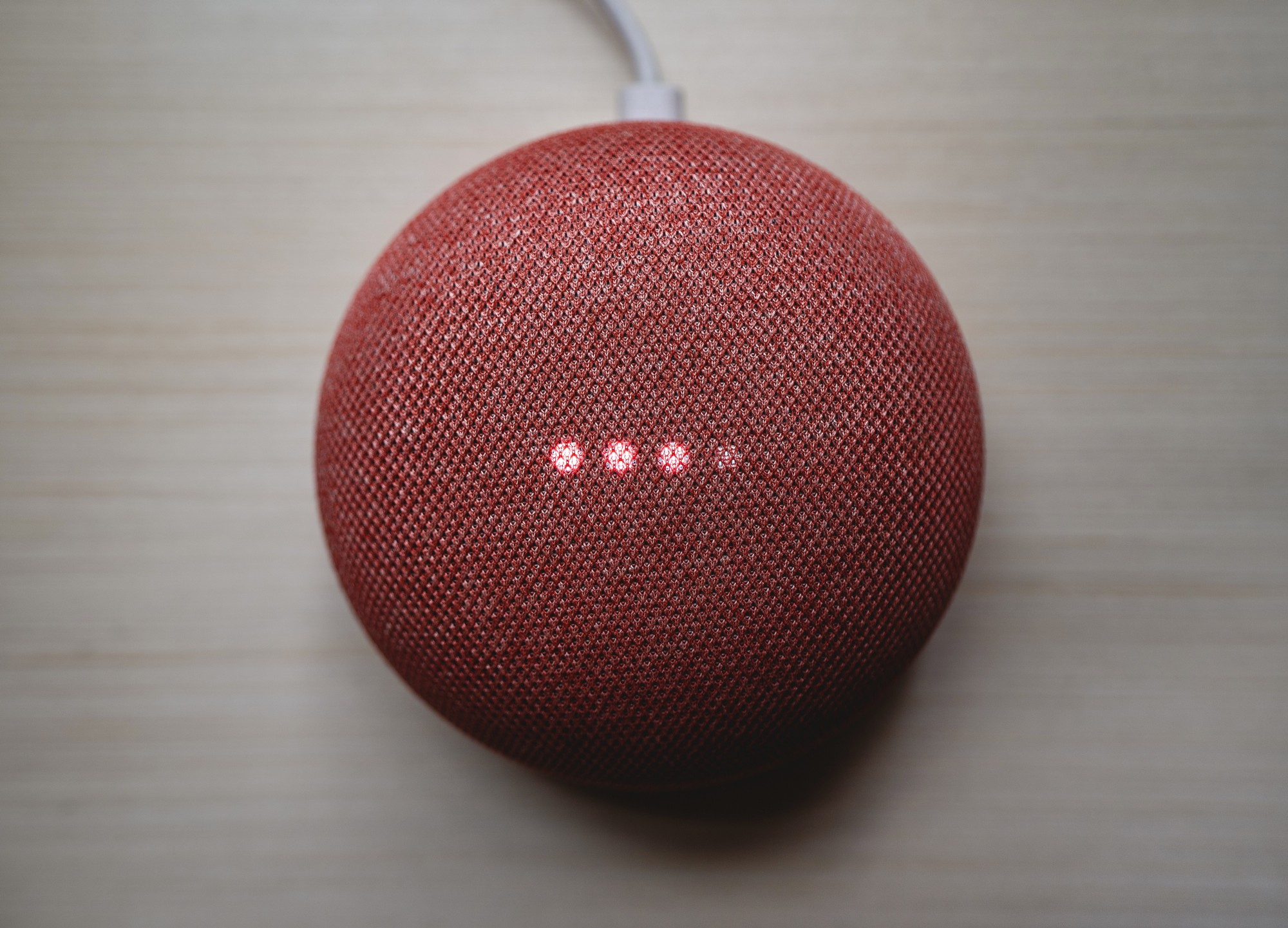 An Alexa-style digital device with three red dots lit up, as it prepares to communicate an answer.