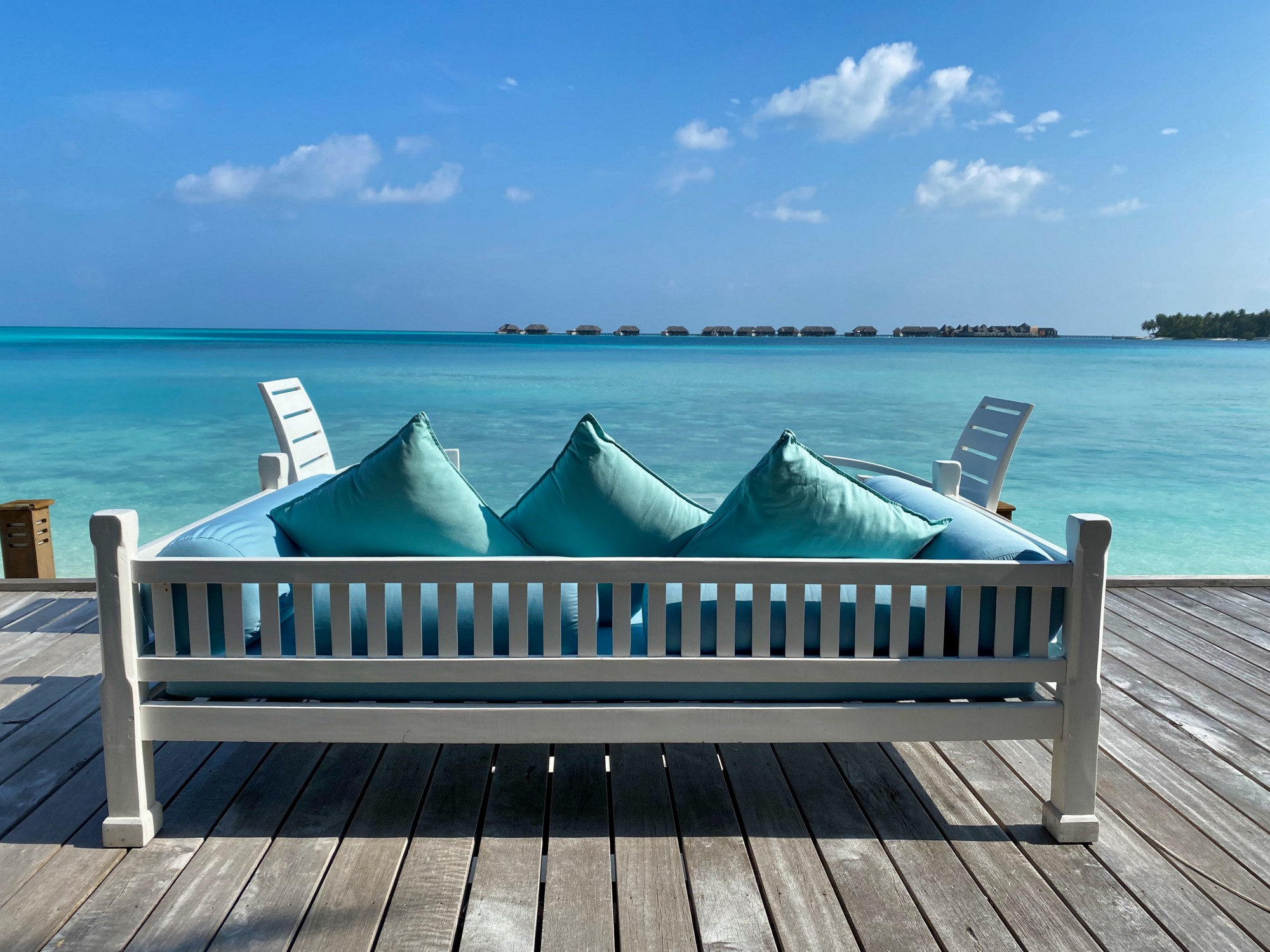 A white bench covered in blue cushions on a deck facing a view of the blue ocean waters