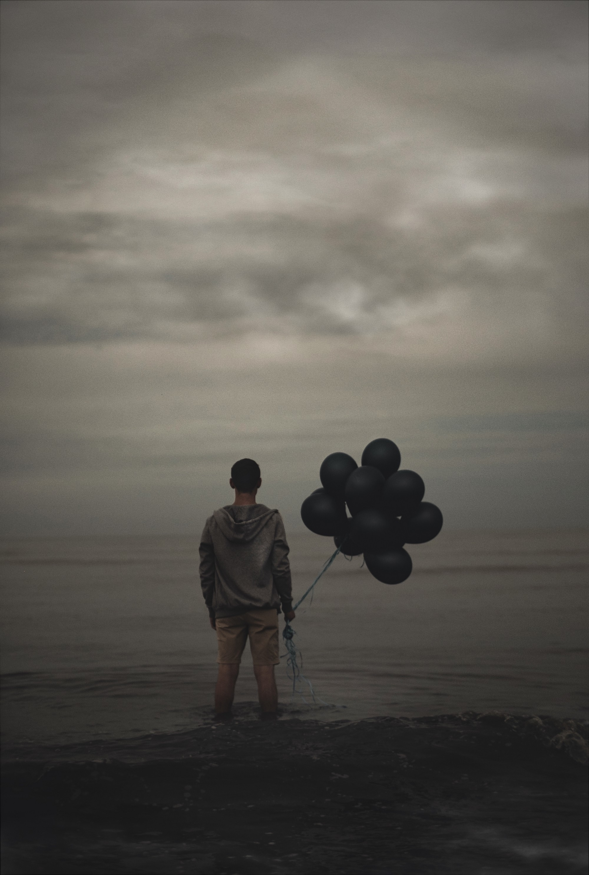 A man holds black balloons while looking out at the water.