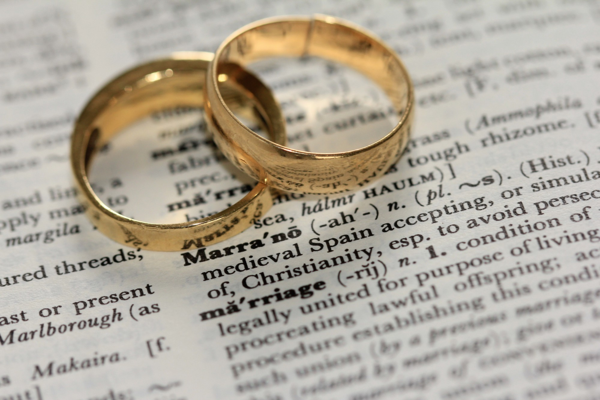 Two wedding rings on top of a dictionary opened to the word marriage