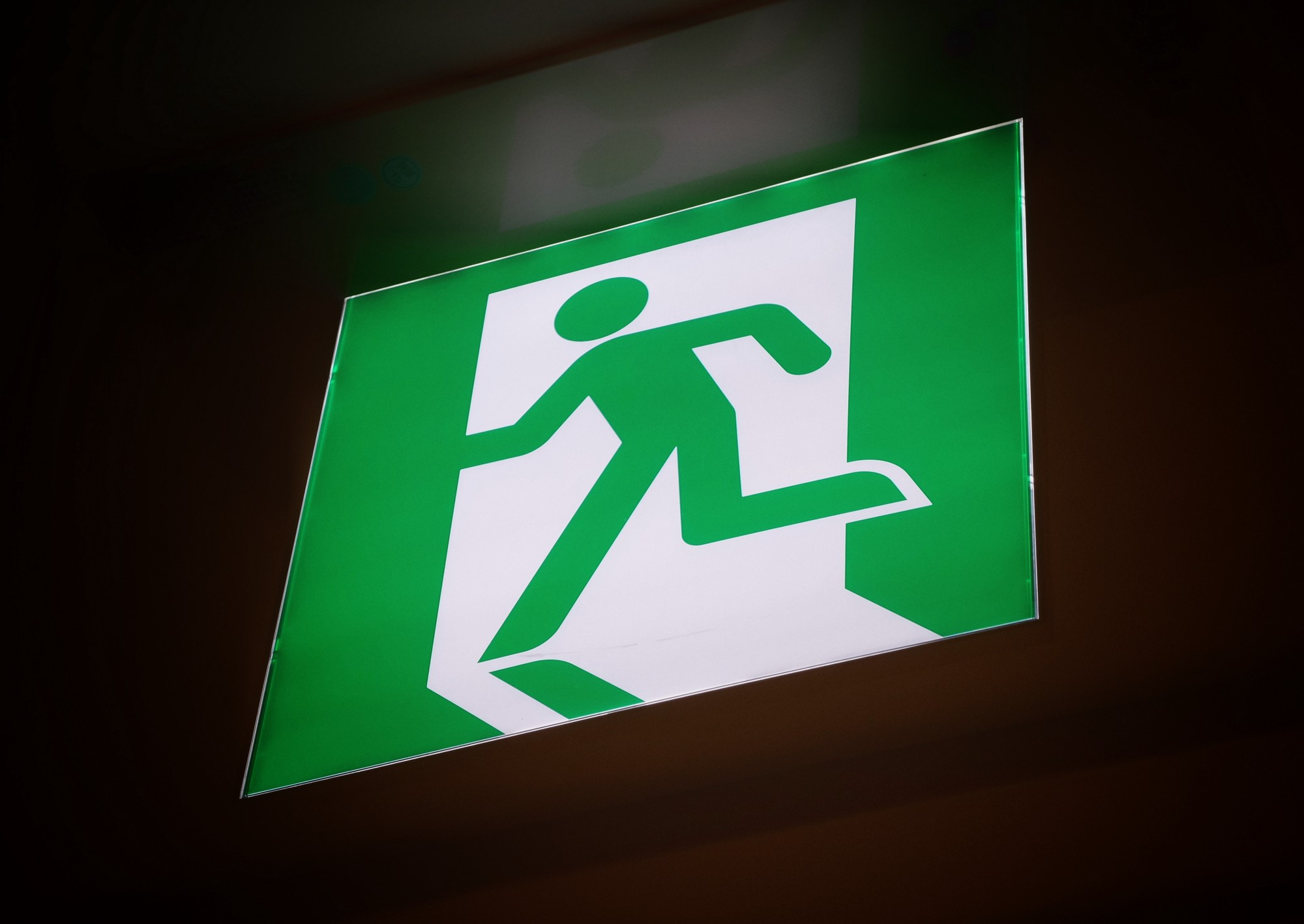 Exit sign with stick figure shown running out the door