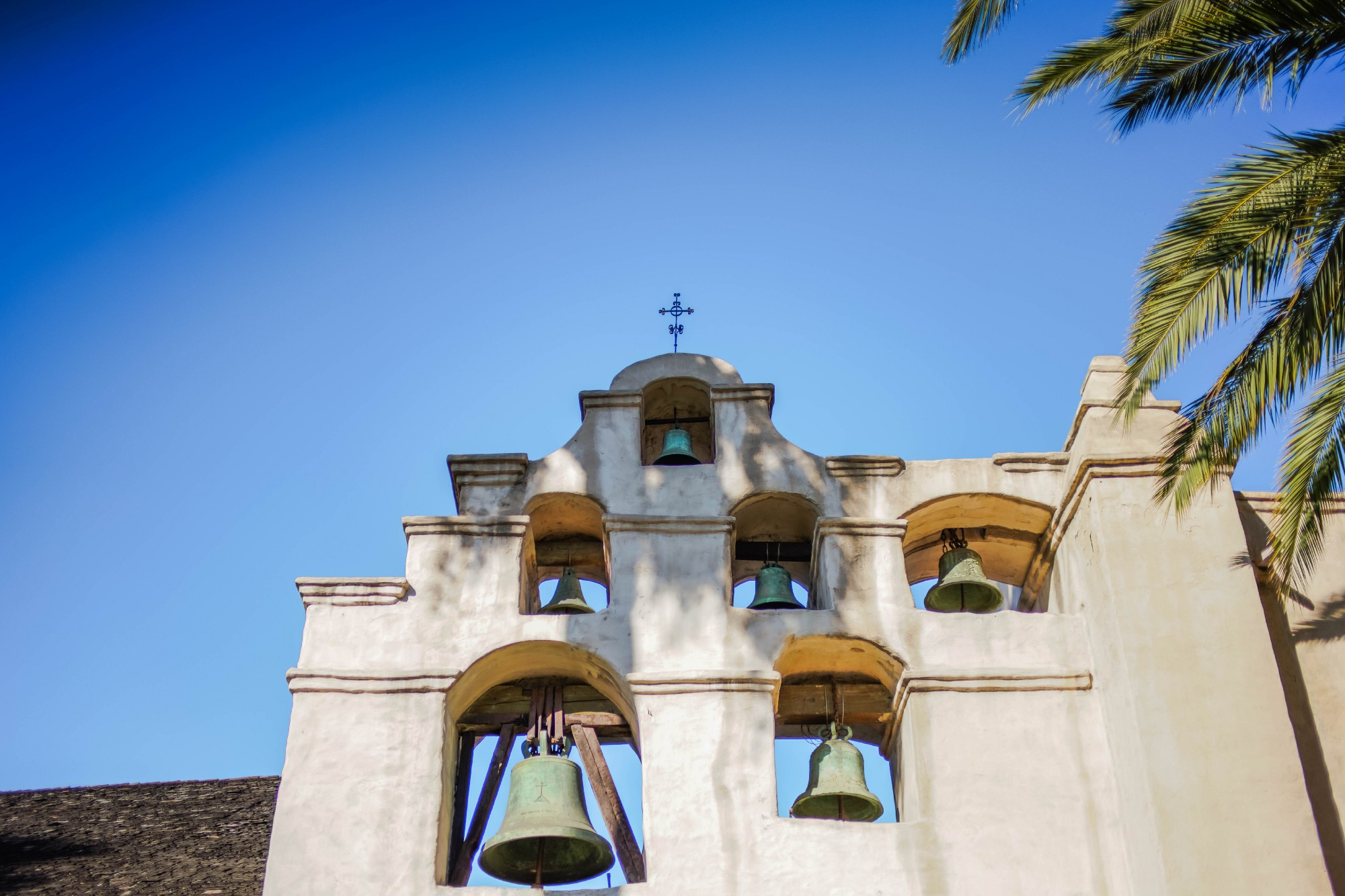 A bell tower with 5 bells embedded in the wall. Blue sky above.