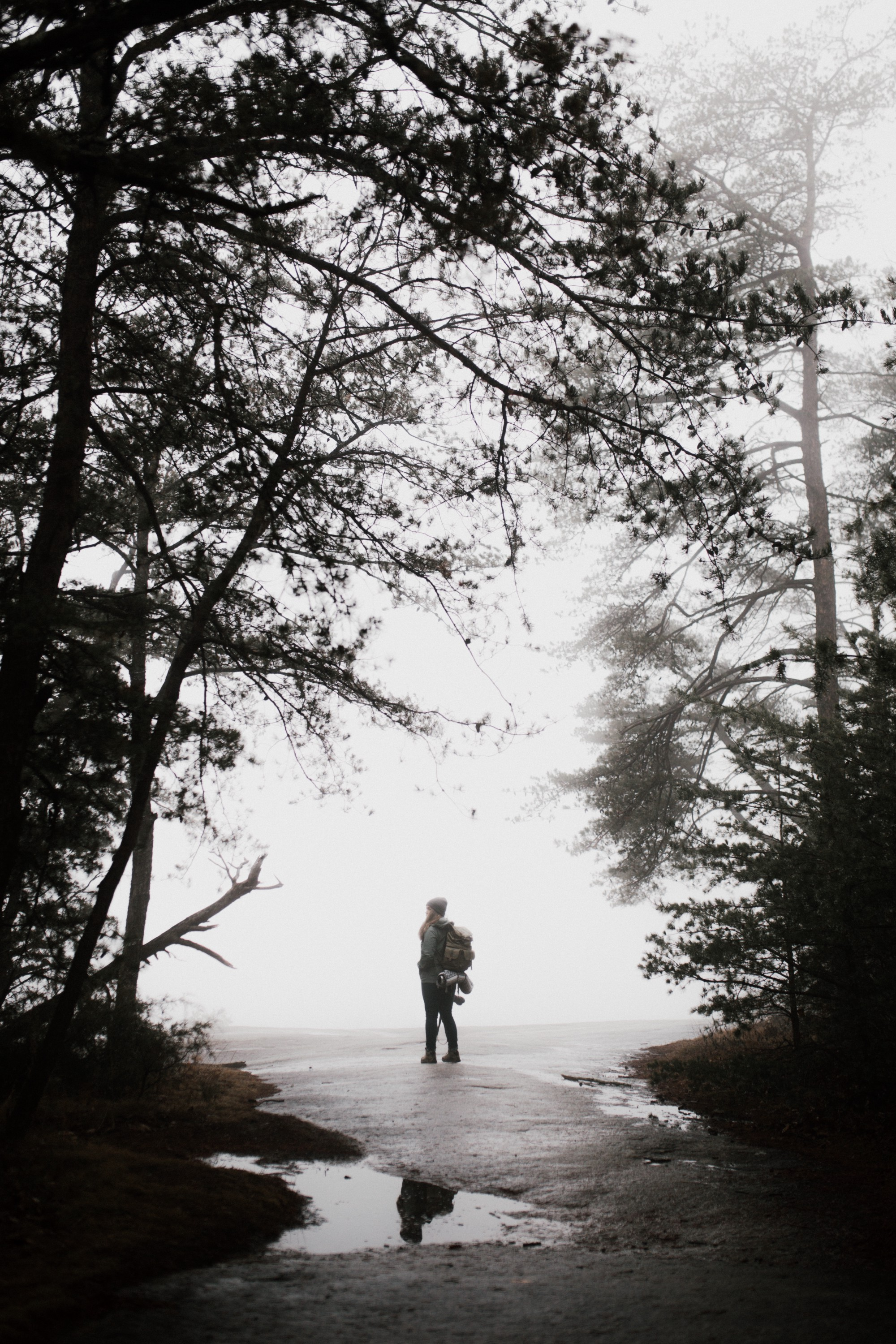 Woman with a backpack stops and looks at a road.