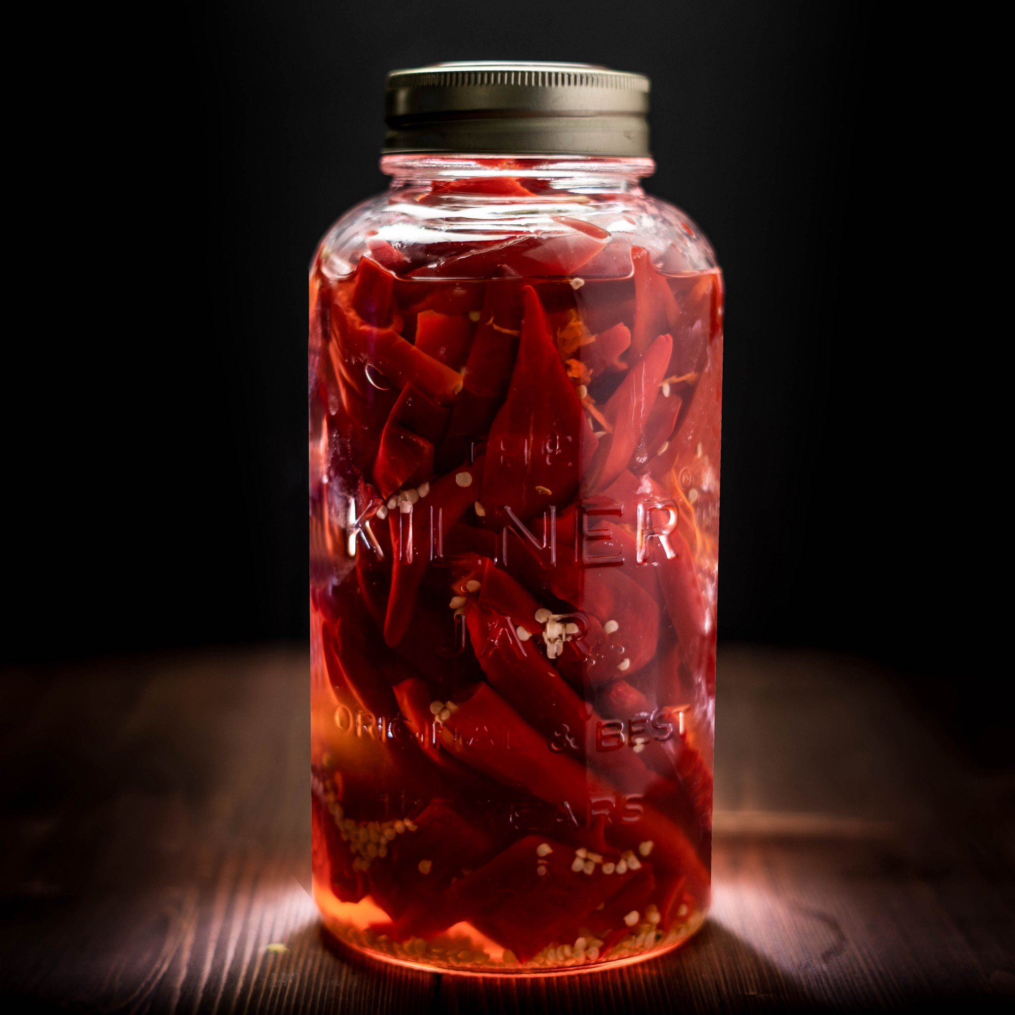 A Kilner jar filled with pickled red chillis