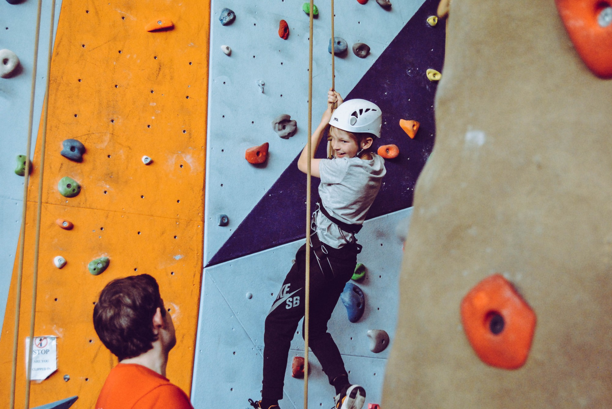 Adult looking at child using ropes on climbing wall.
