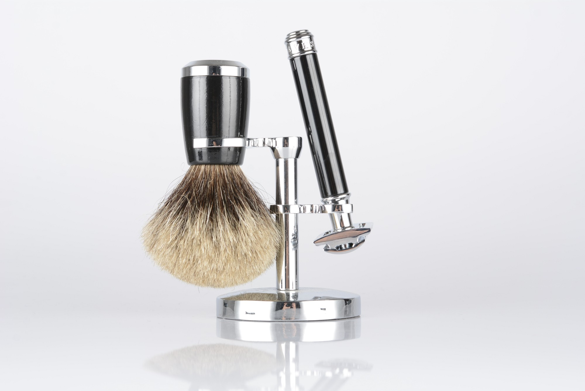 A razor and shaving cream brush on a stand