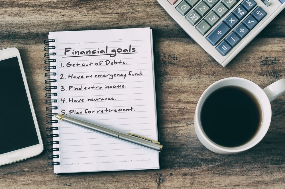 Financial goals on notepad on blank notepad with calculator, coffee, pen and smart phone on a wooden table, retro style