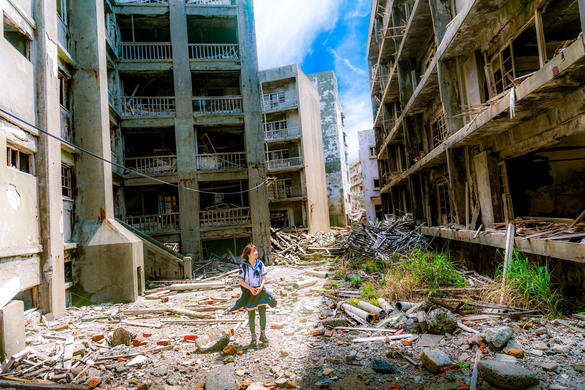 A woman standing in the middle of rubble from destroyed buildings