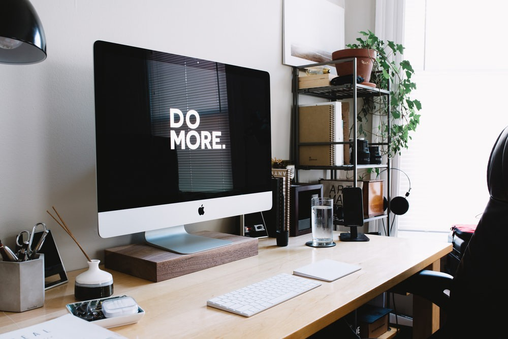 "Inside a home office, a monitor on the desk has a screensaver that says, ""DO MORE.'"