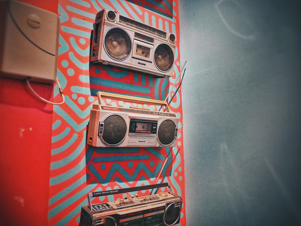 Three gray boomboxes hanging from wall