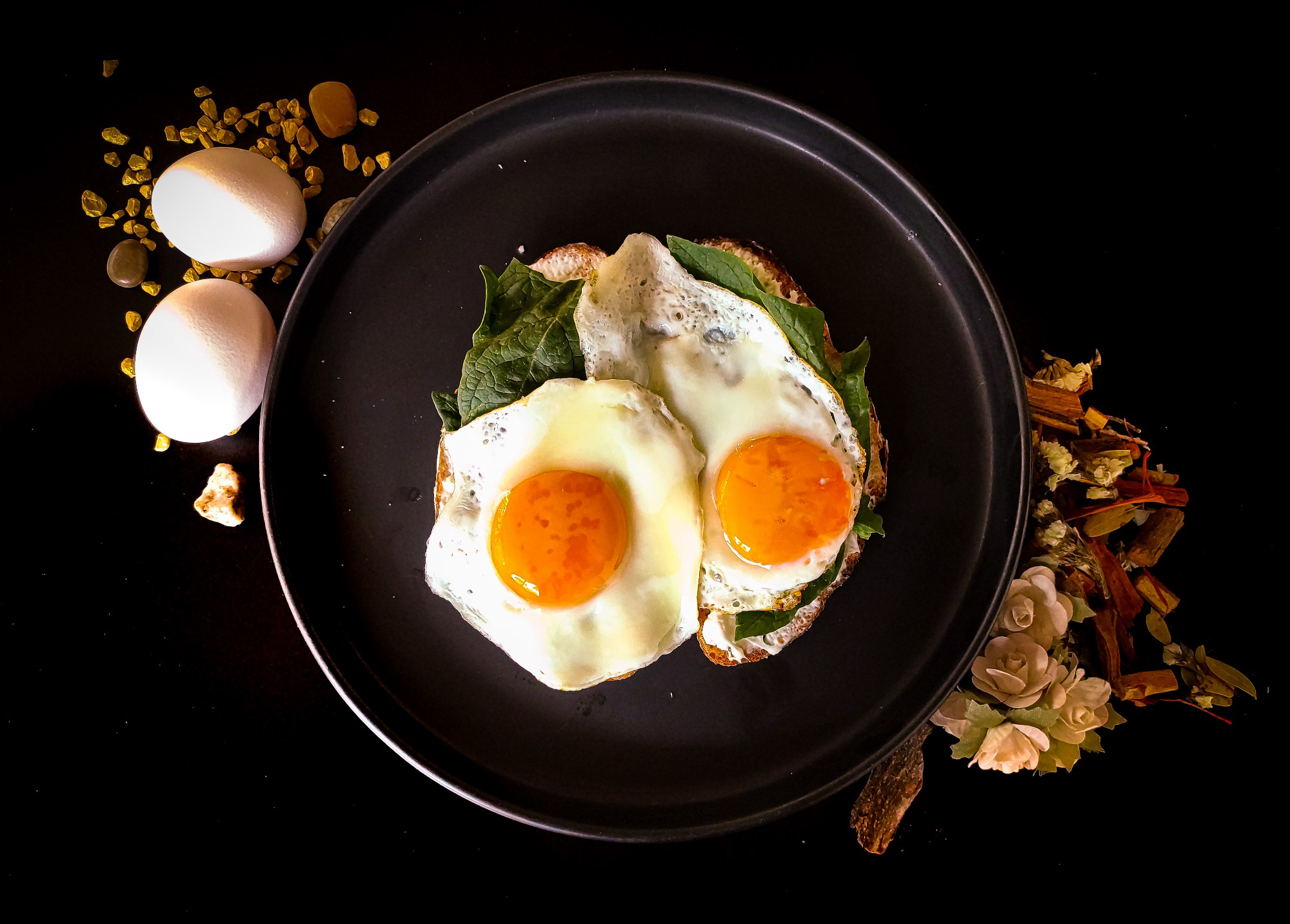 the image is that of two fried eggs in a pan; on the side are two more eggs as if waiting their turn and the images is complete with what appears to be nuts and flowers on the side for decorative purposes