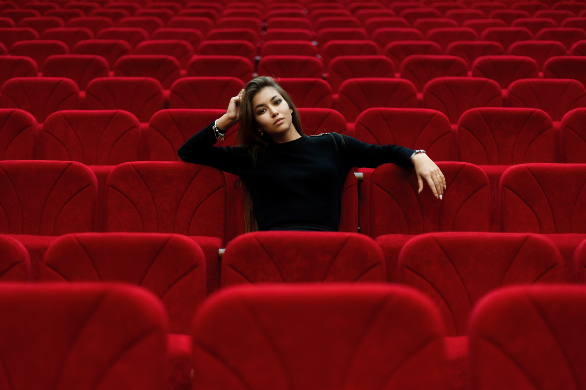 A lone woman sitting in a movie theater waiting to be intrigued