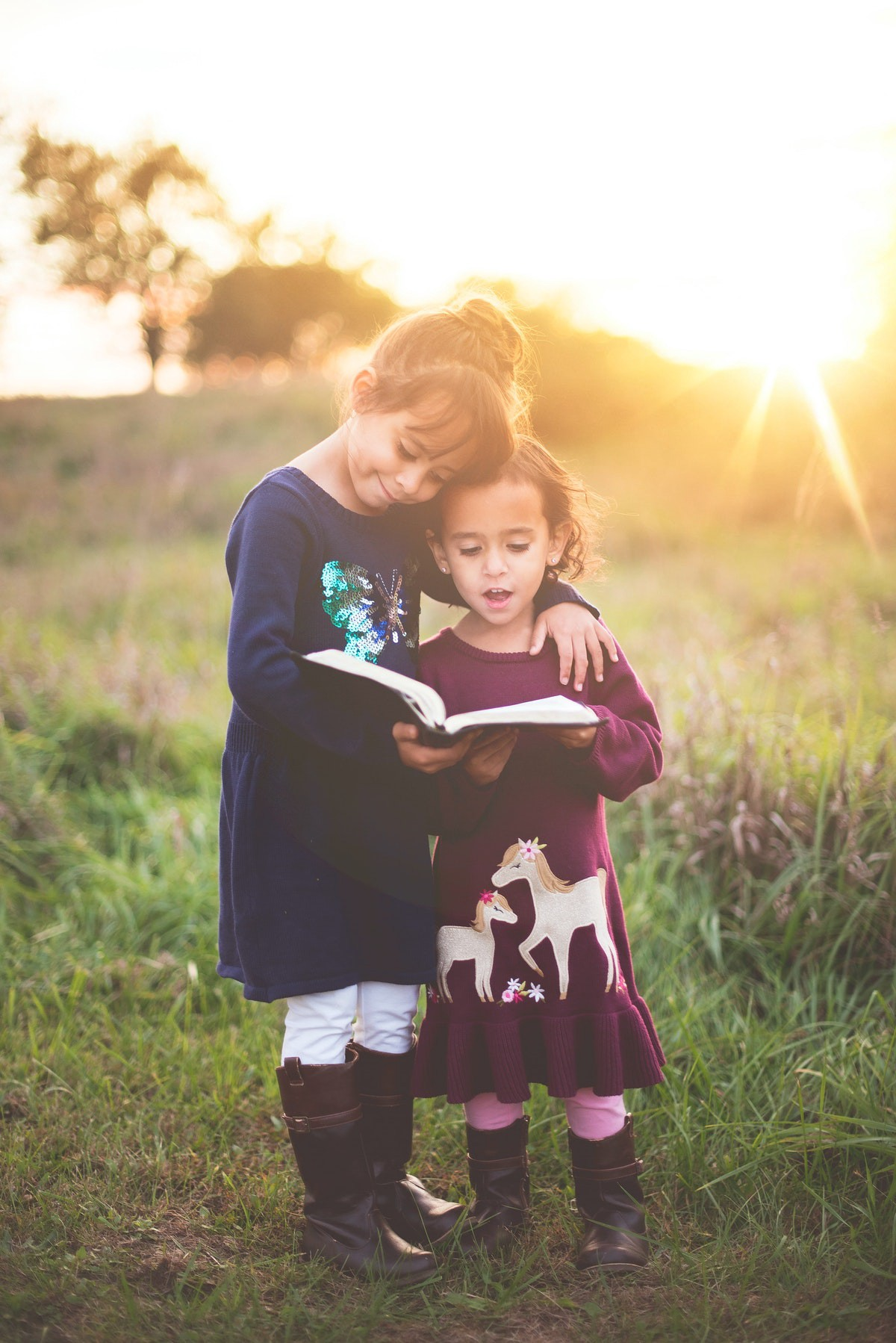 Two young girls reading the Bible.