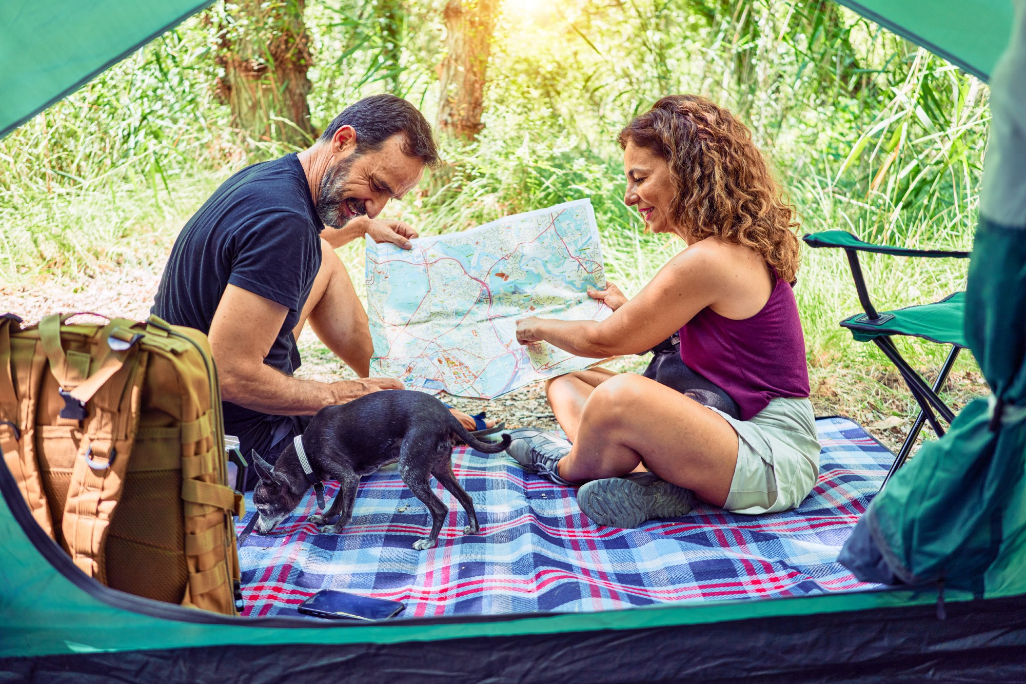 A couple enjoying their picnic with their dog