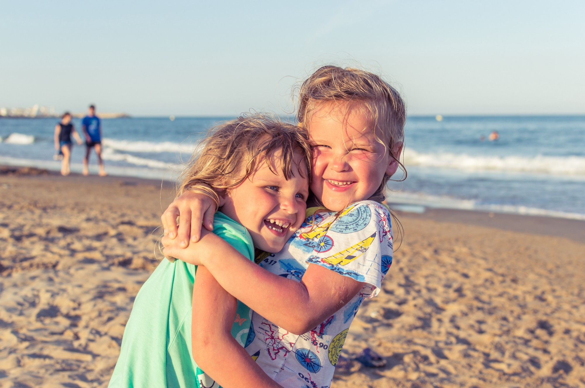Two girls hugging at the beach
