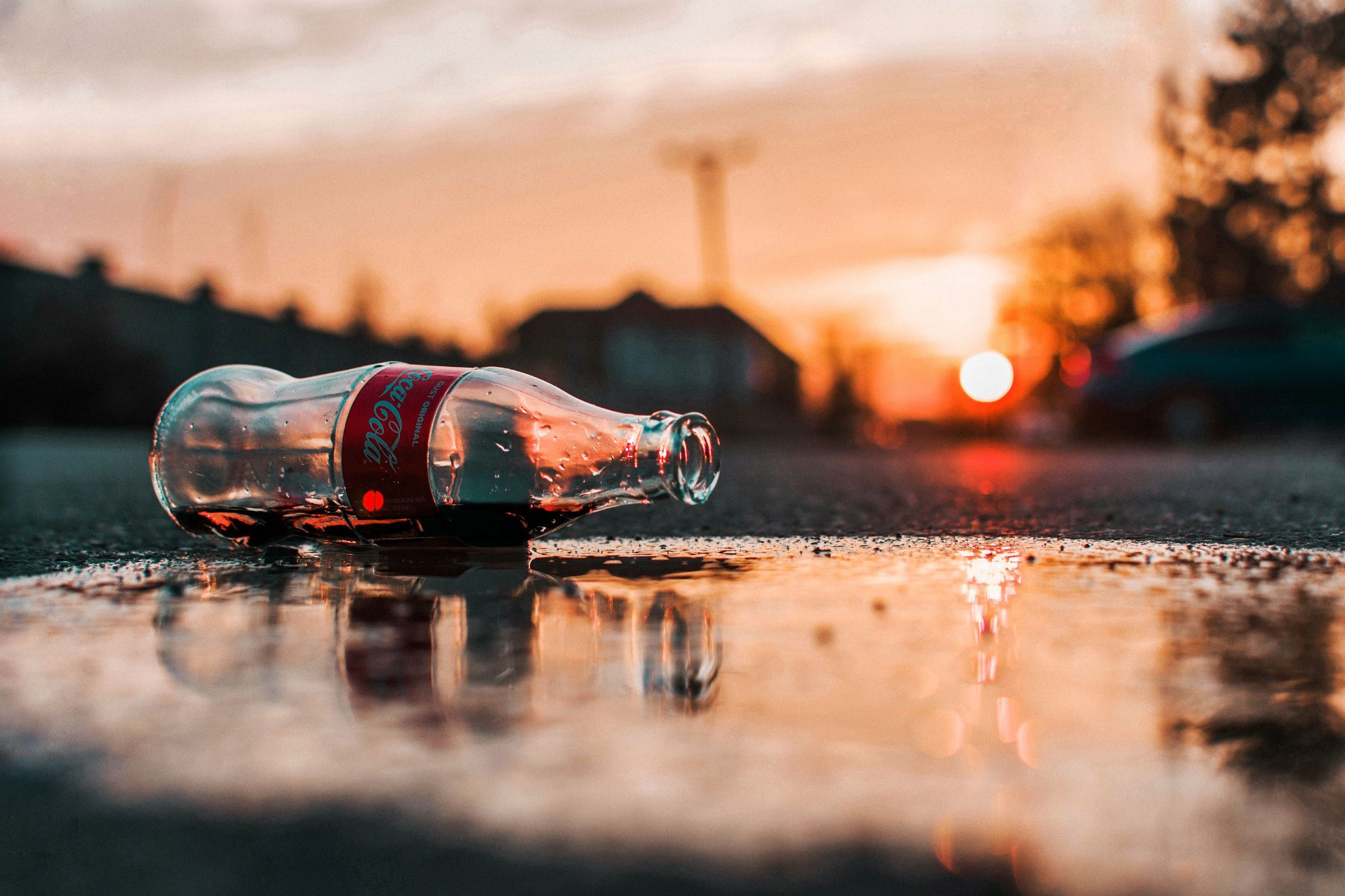 An opened Glass Coke bottle on the ground near a puddle of Coke. Sun is setting in the background.