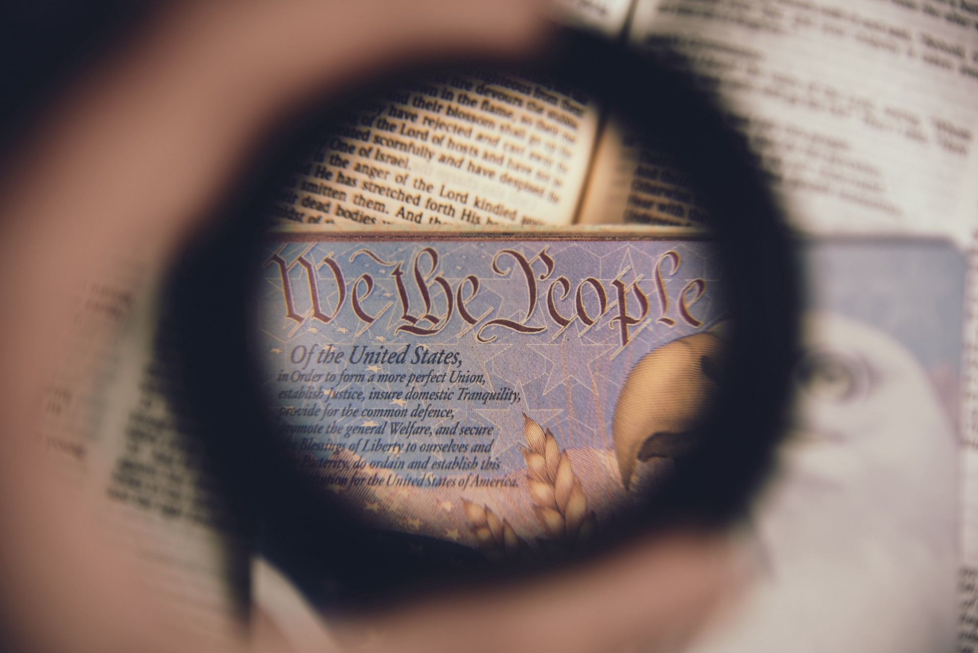 A human hand holding a lens over the opening words of the US Constitution.