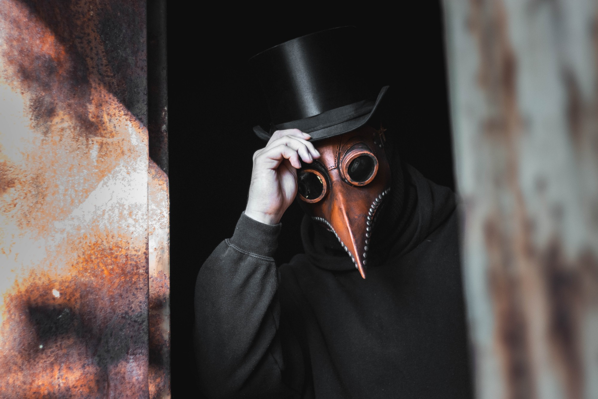 A person in a black hoodie wearing a top hat and a beaked mask in the style of headgear worn by doctors during the black plague.