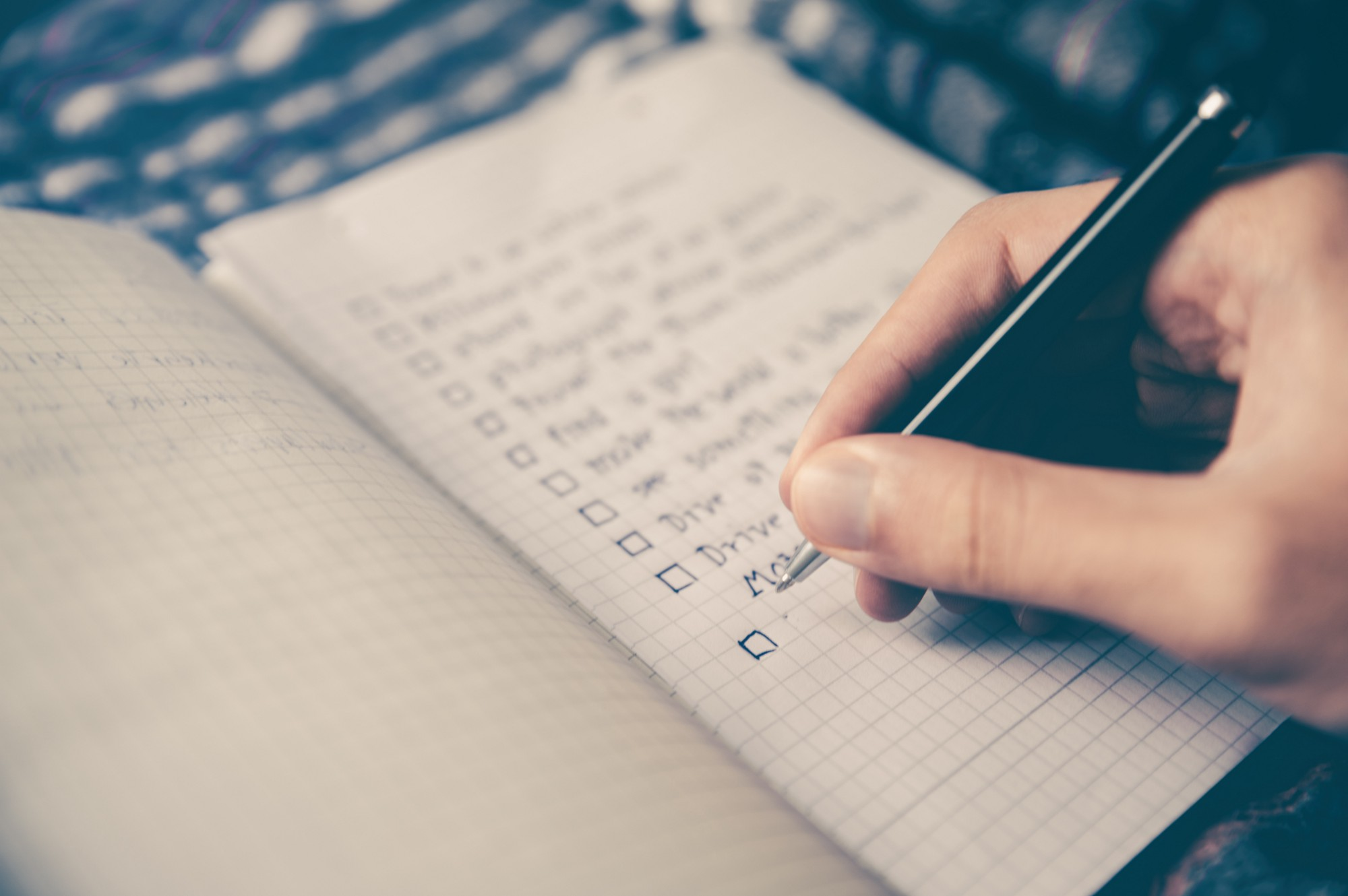 A white hand holds a pen over an open notebook. The page shows a number of items written into a checklist.