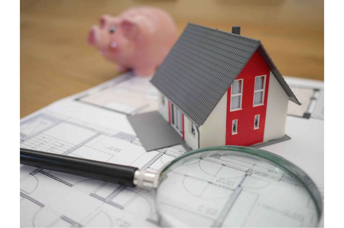 Model of a home sitting on top of blueprints, with a piggy bank in the background.