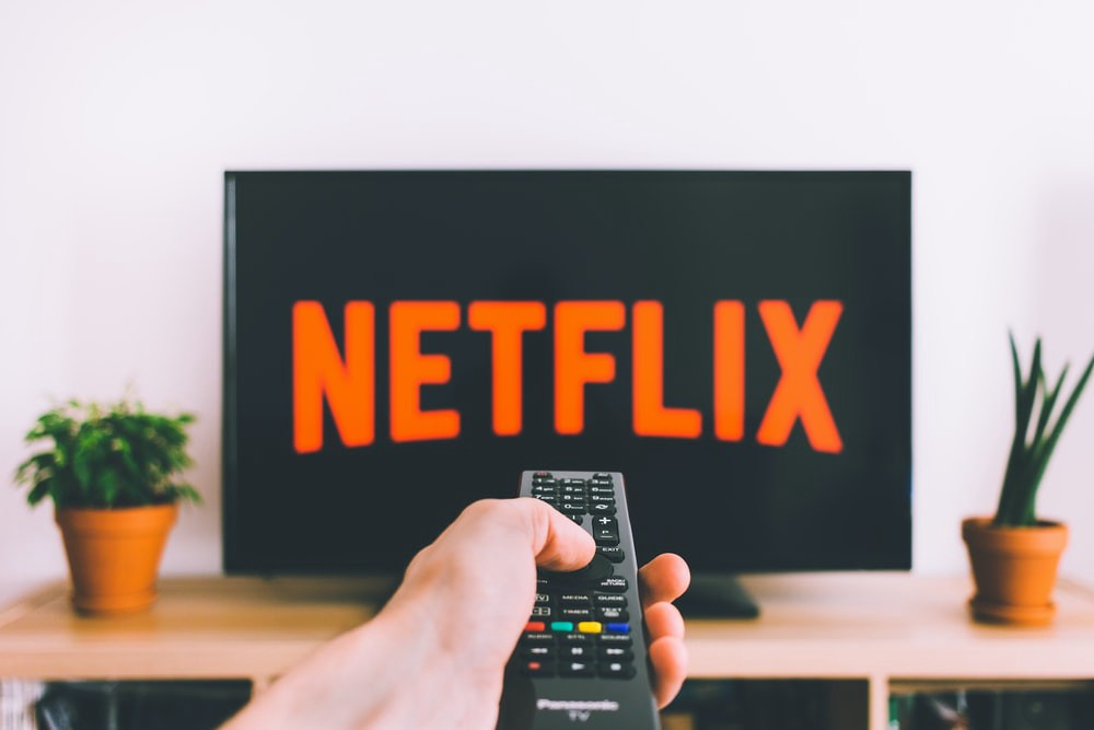 Person holding remote pointing at a TV with Netflix on the screen