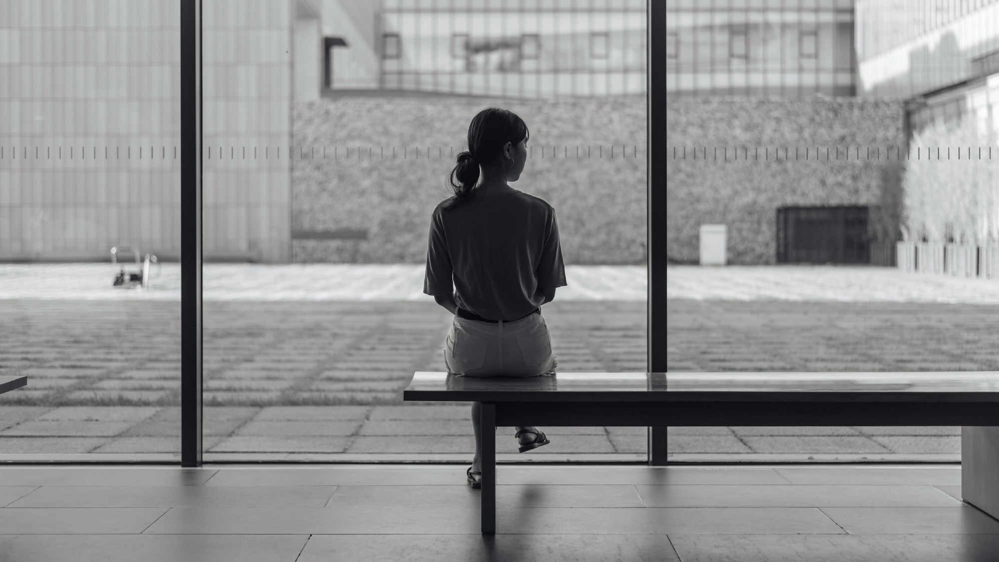 lonely girl sitting on bench alone black and white photo