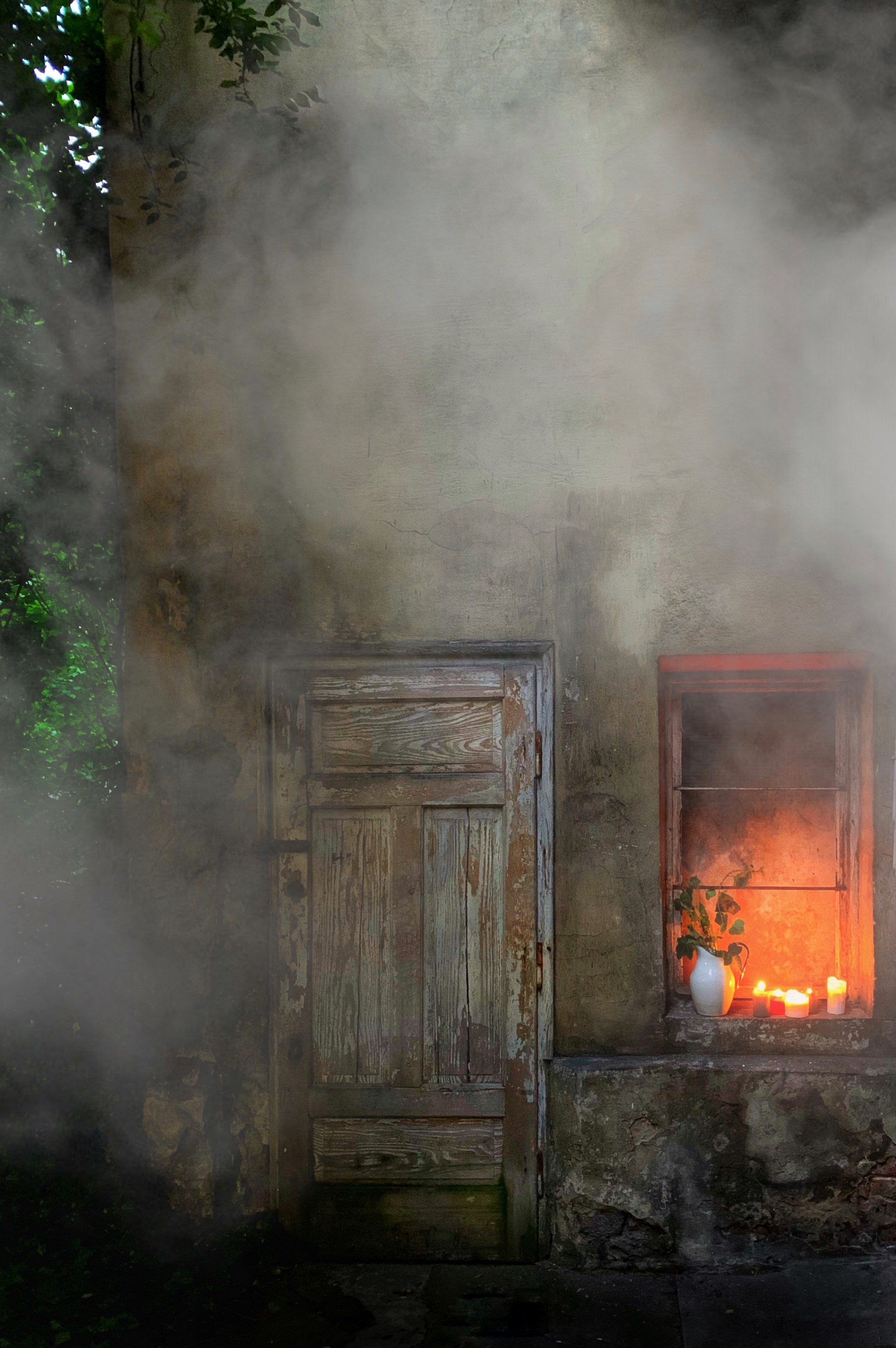The front of a small old house shrouded in smoke, fire light seen through the window.