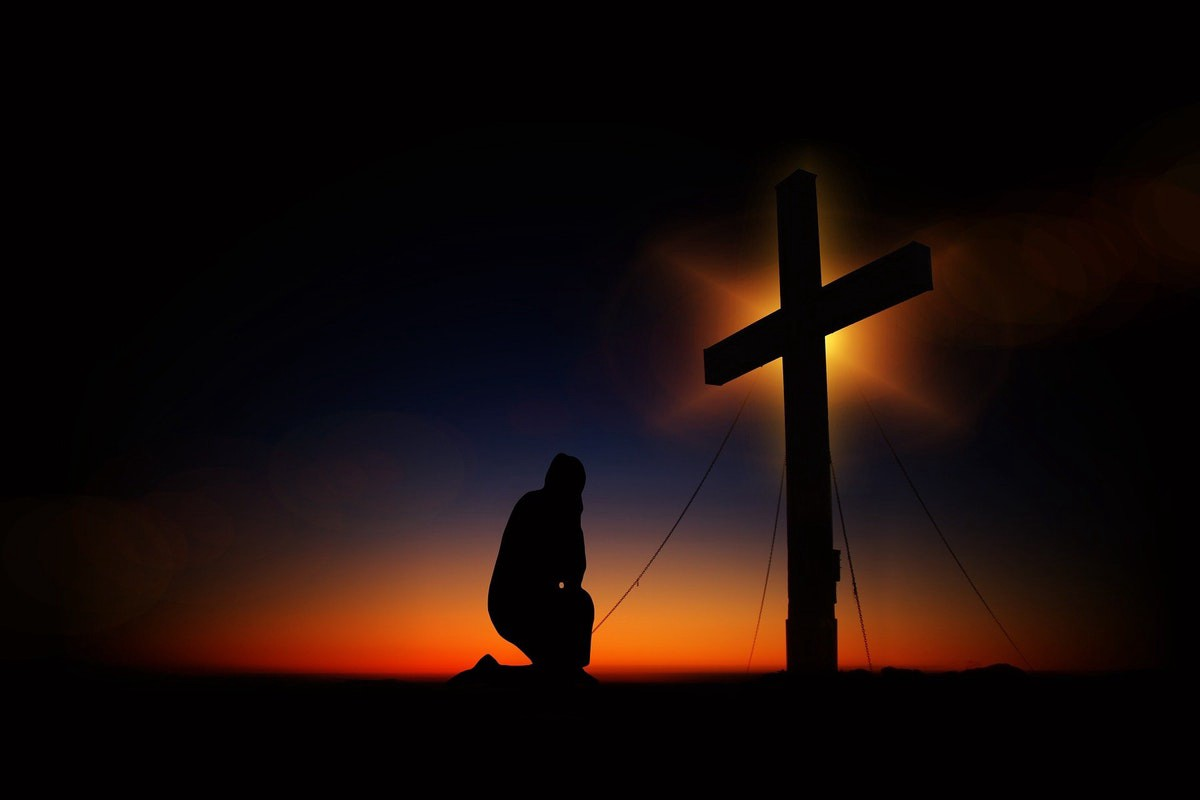 Silhouette of a man kneeling before a cross with a darkish background