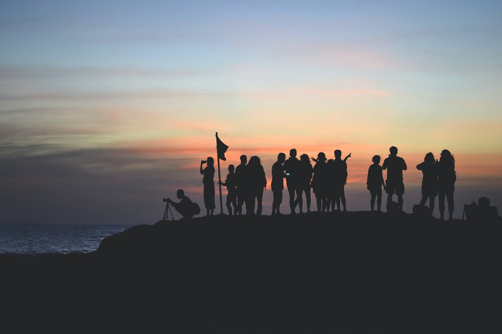 a group of people in the shadow of the sunset captured in Indonesia