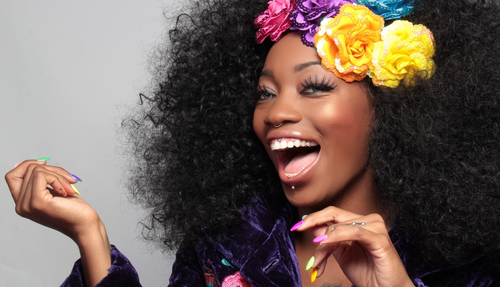 A beautiful dark-skinned woman with flowers in her hair is smiling.