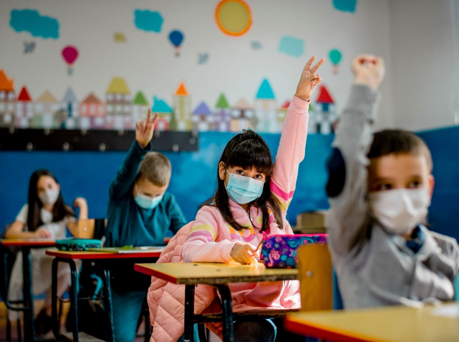Kids wearing face masks raising their hands in an elementary school classroom. Photo by kevajefimija/Getty Images