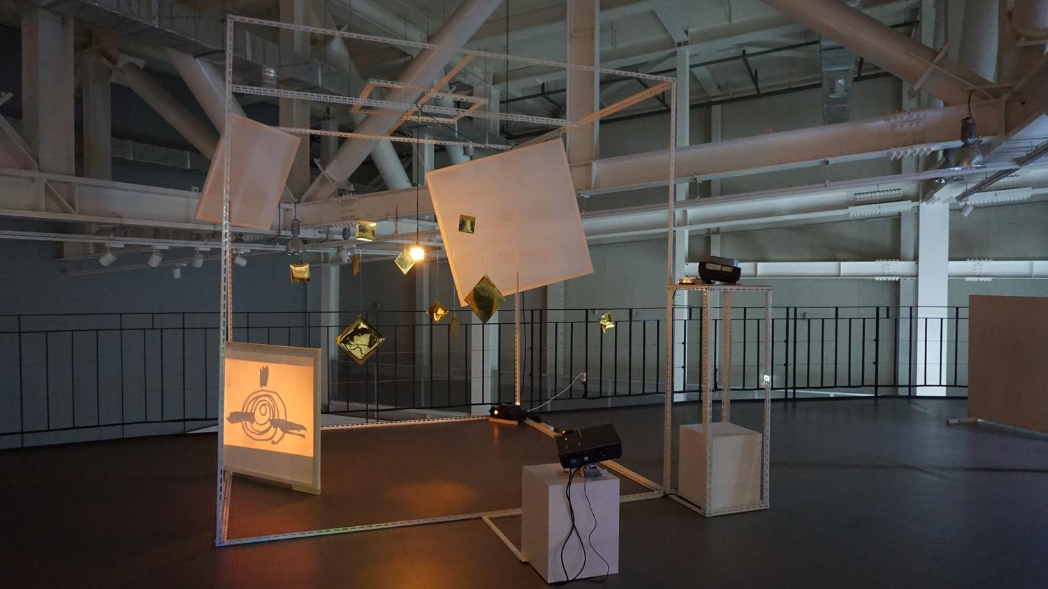 An installation with two projectors on plinths, several hanging lights and screens, within a outlined cube of a room.