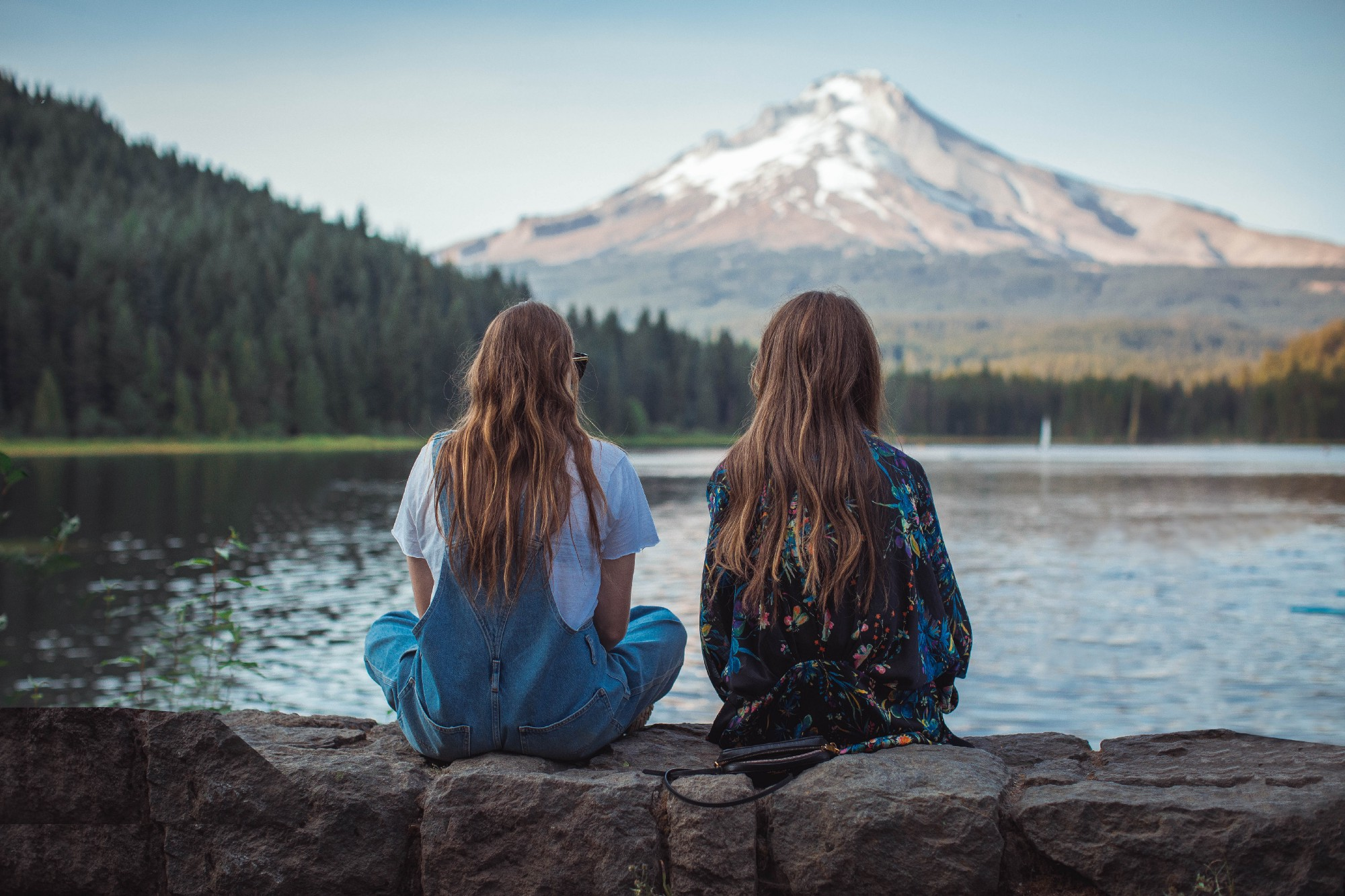 Two women sitting on pier overlooking lake and mountains.