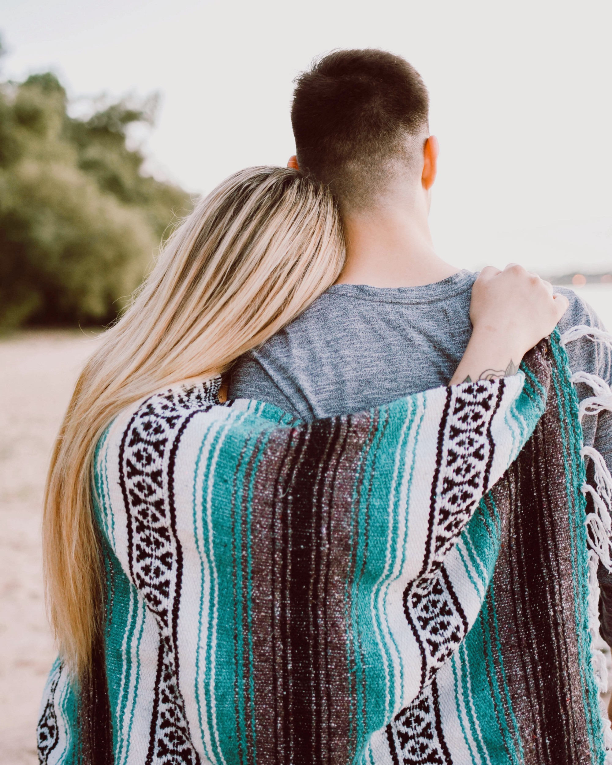 A man and woman hugging with a blue patterned blanket