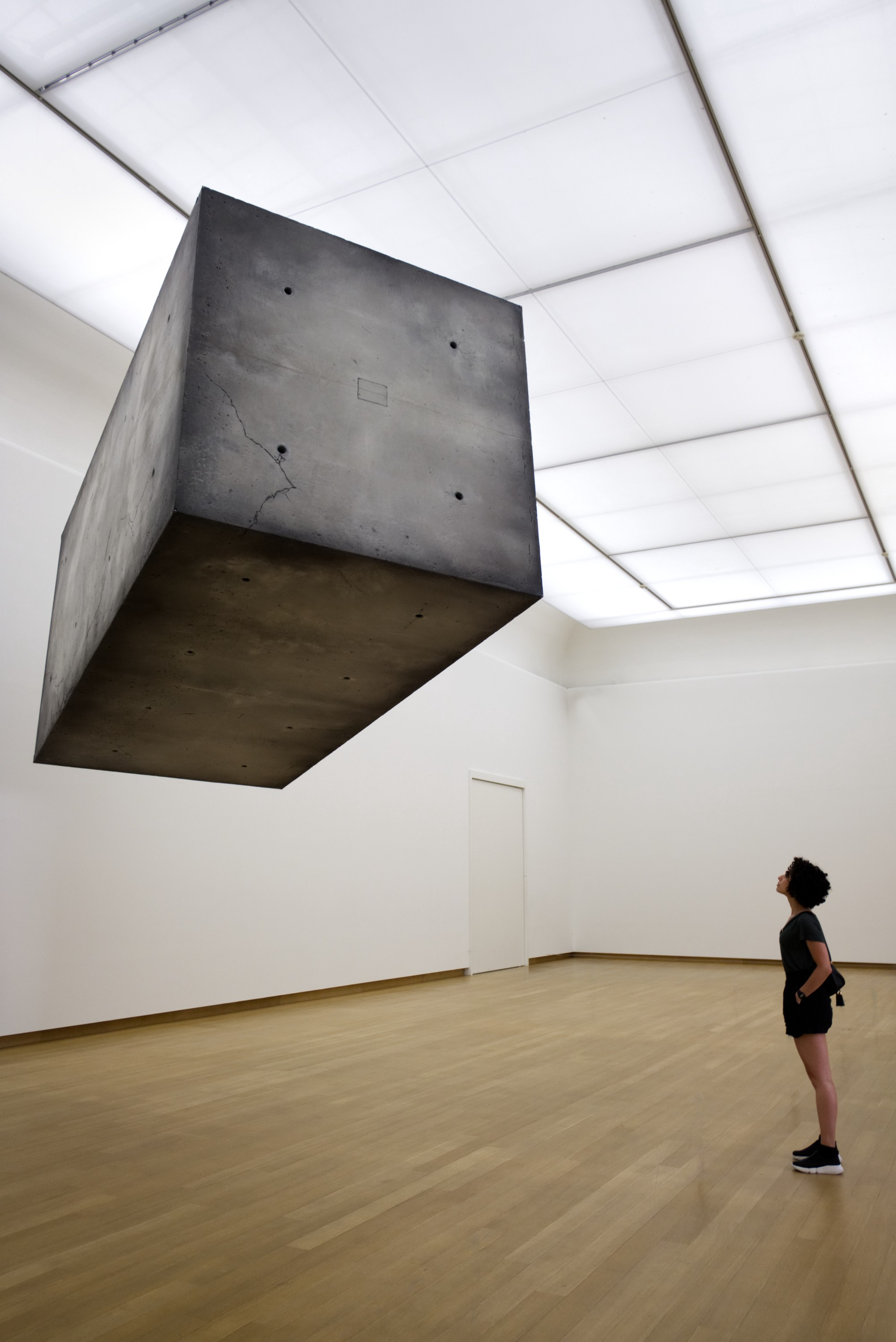 greyish cement cube floating 10 feet in the air, in a well lit, white room.