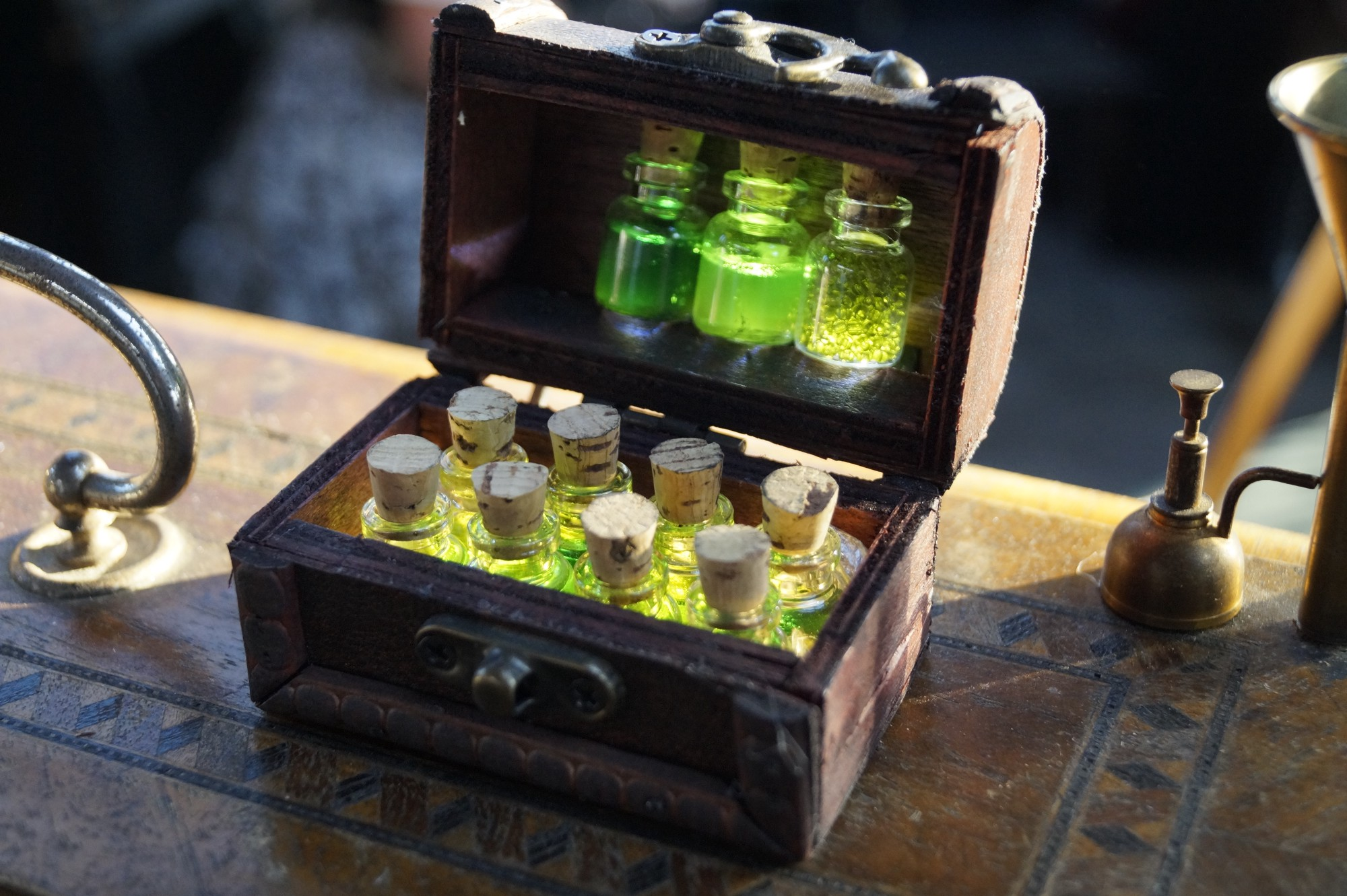 A small wooden chest full of small bottles filled with green liquid
