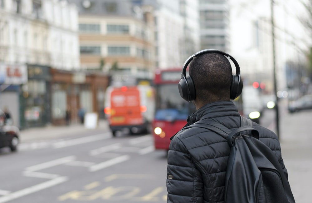 Man wearing leather jacket while listening to headphones