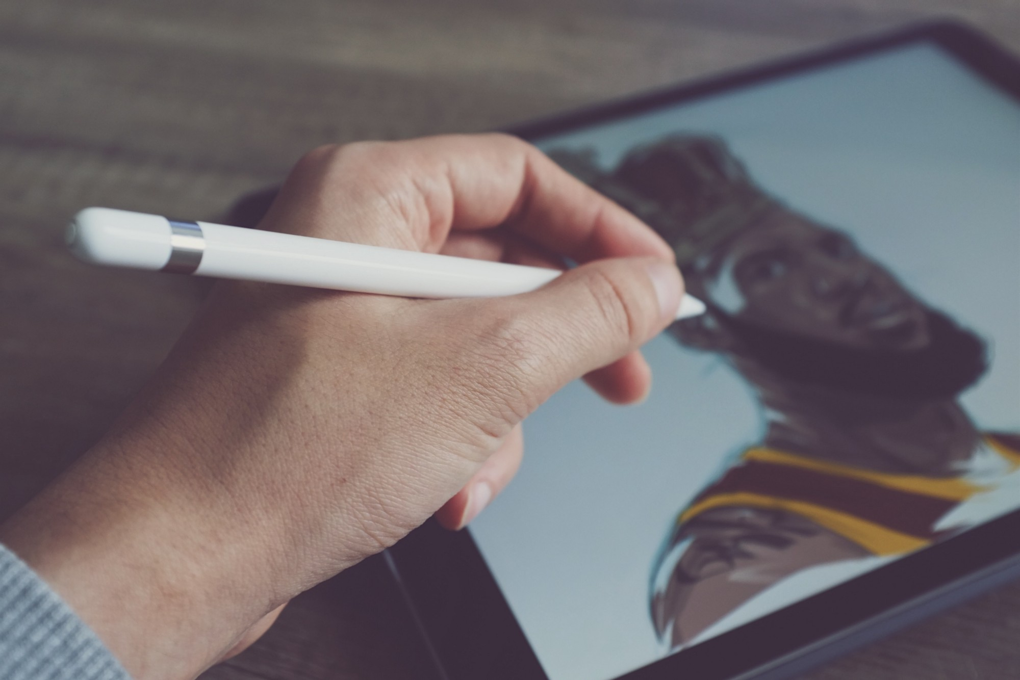 someone using an apple pencil with an ipad, drawing an illustration of a man