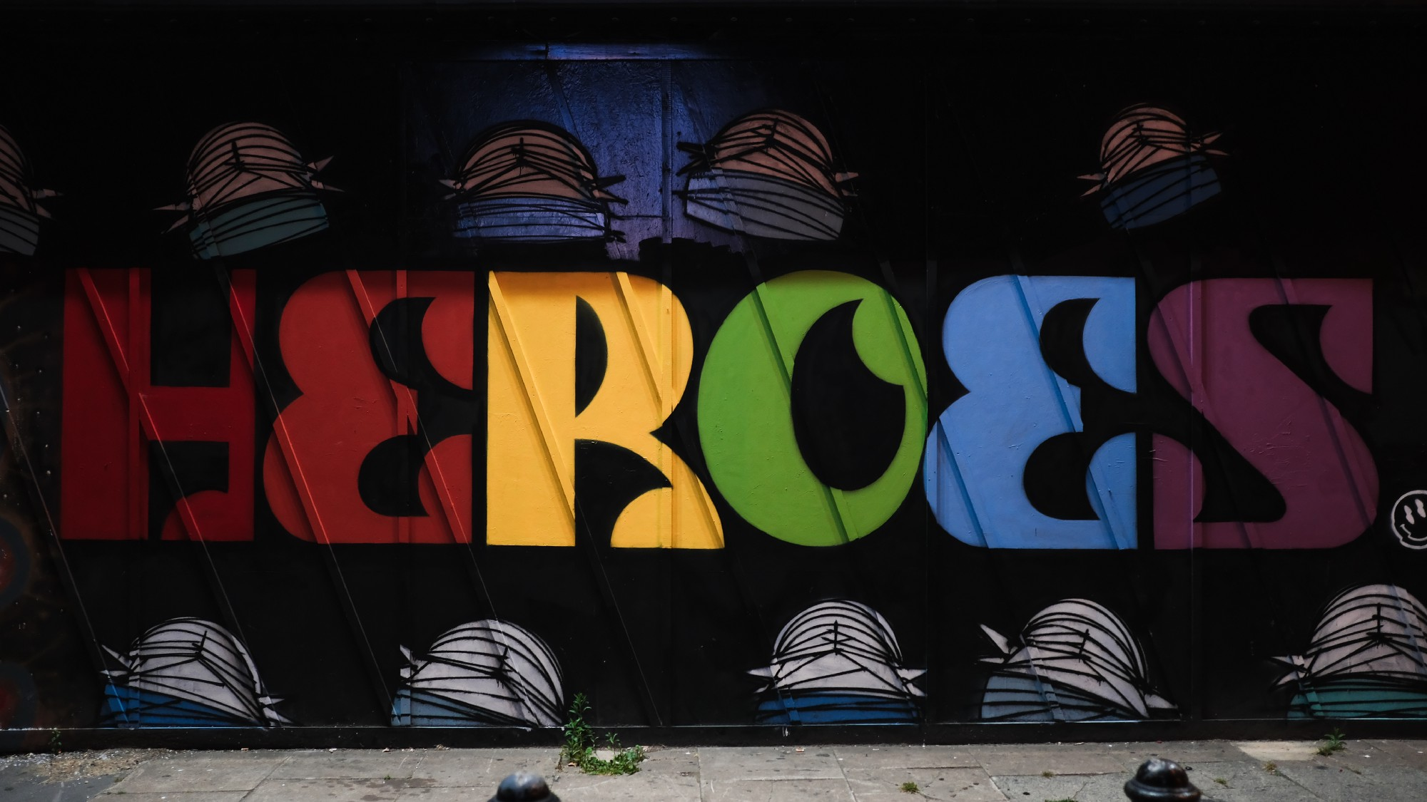 Multicolored letters spell out HEROES on a black background, with a border of hats or masks at top and bottom.