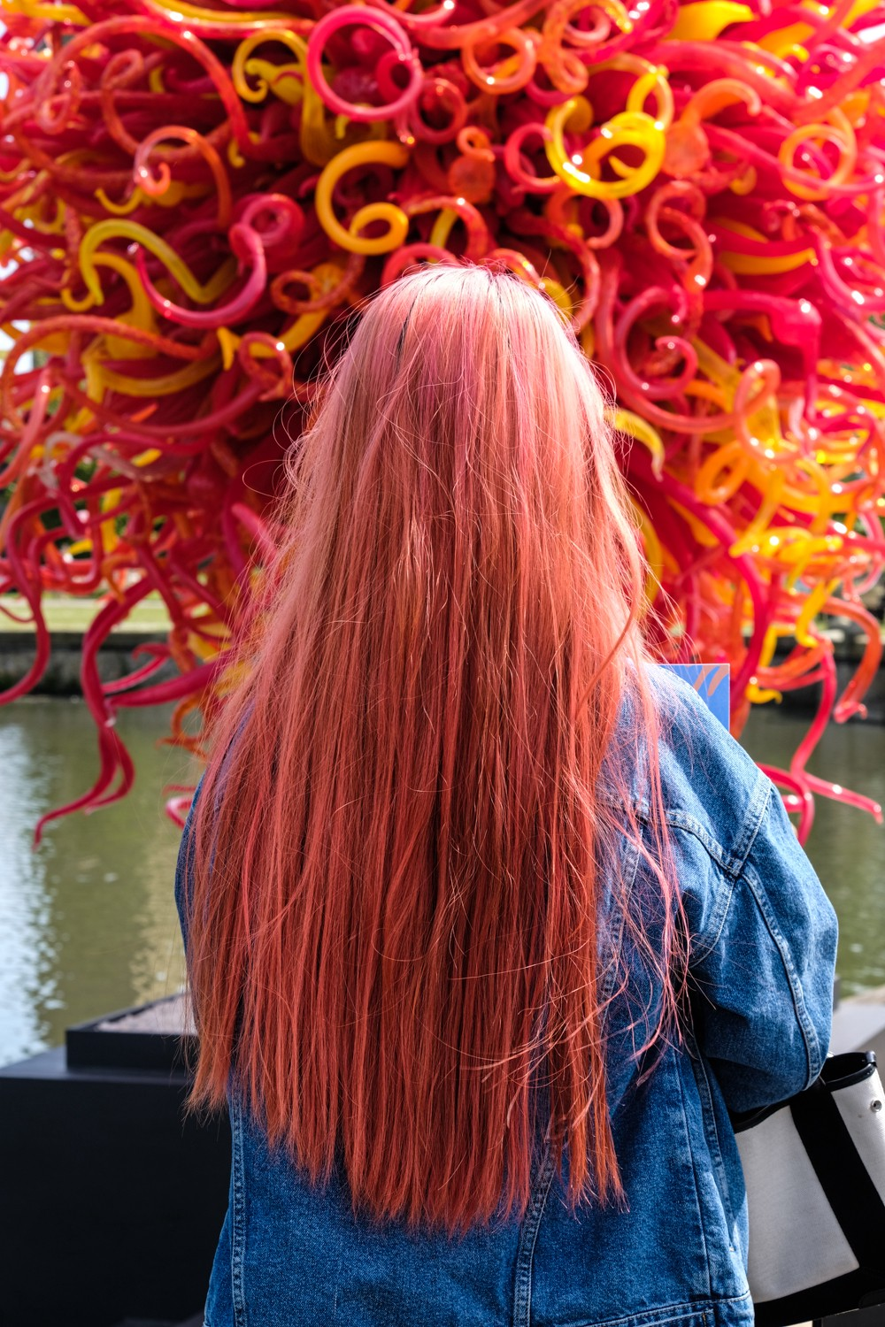 Chihuly glass sculpture Kew Gardens and girl with coral hair