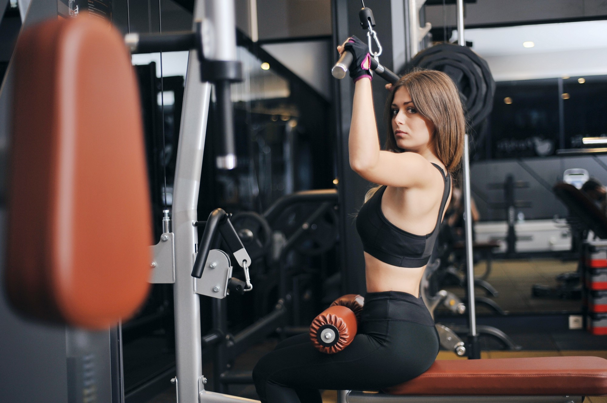 A woman lifting weights looks to her left with a skeptical expression on her face.