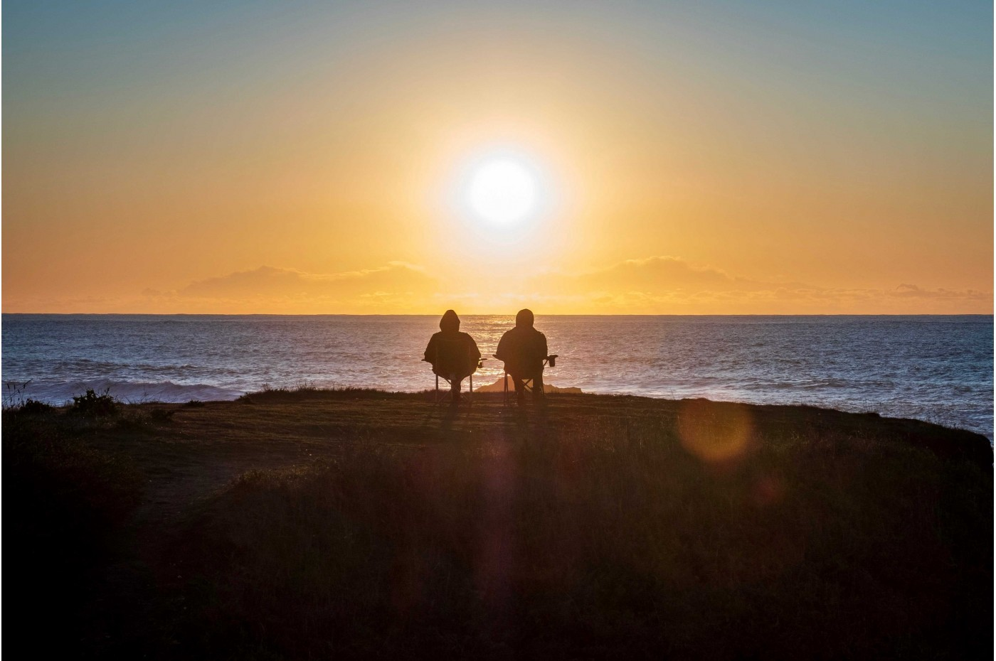 A couple sitting at the oceanfront, watching the sun setting over the water.